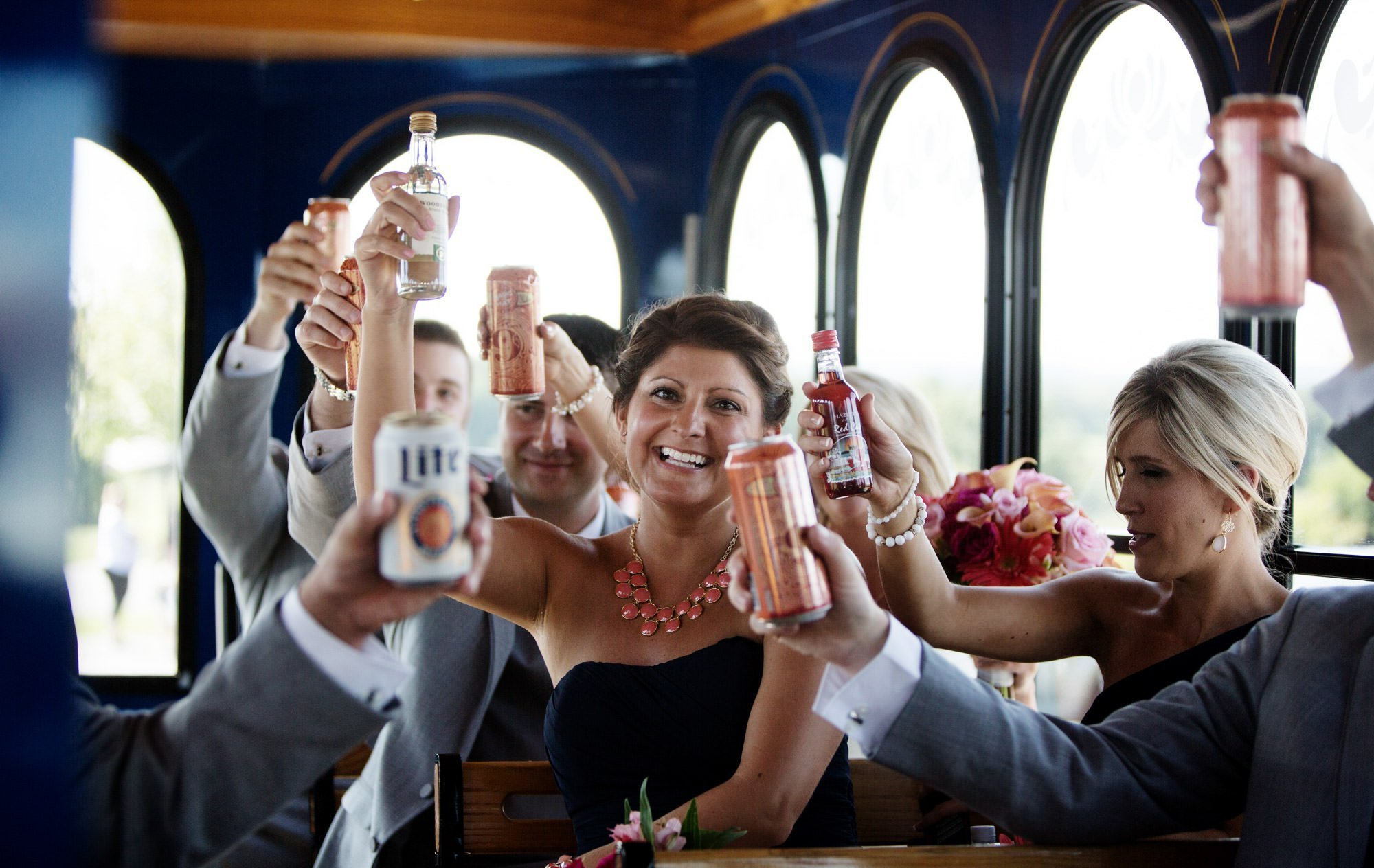 The wedding party cheers on the trolley.