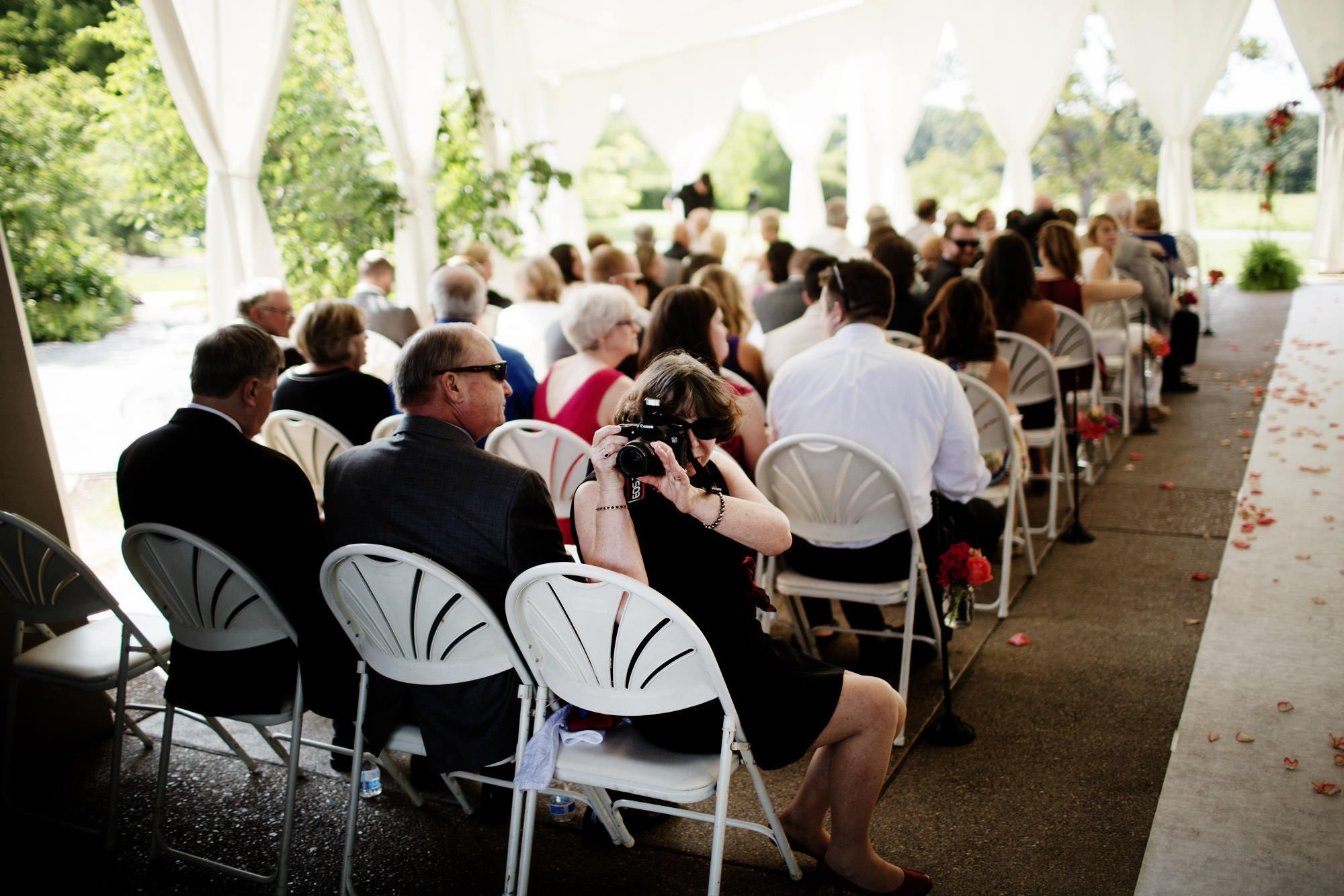Guests take photos prior to the wedding ceremony at the Penn State Arboretum.