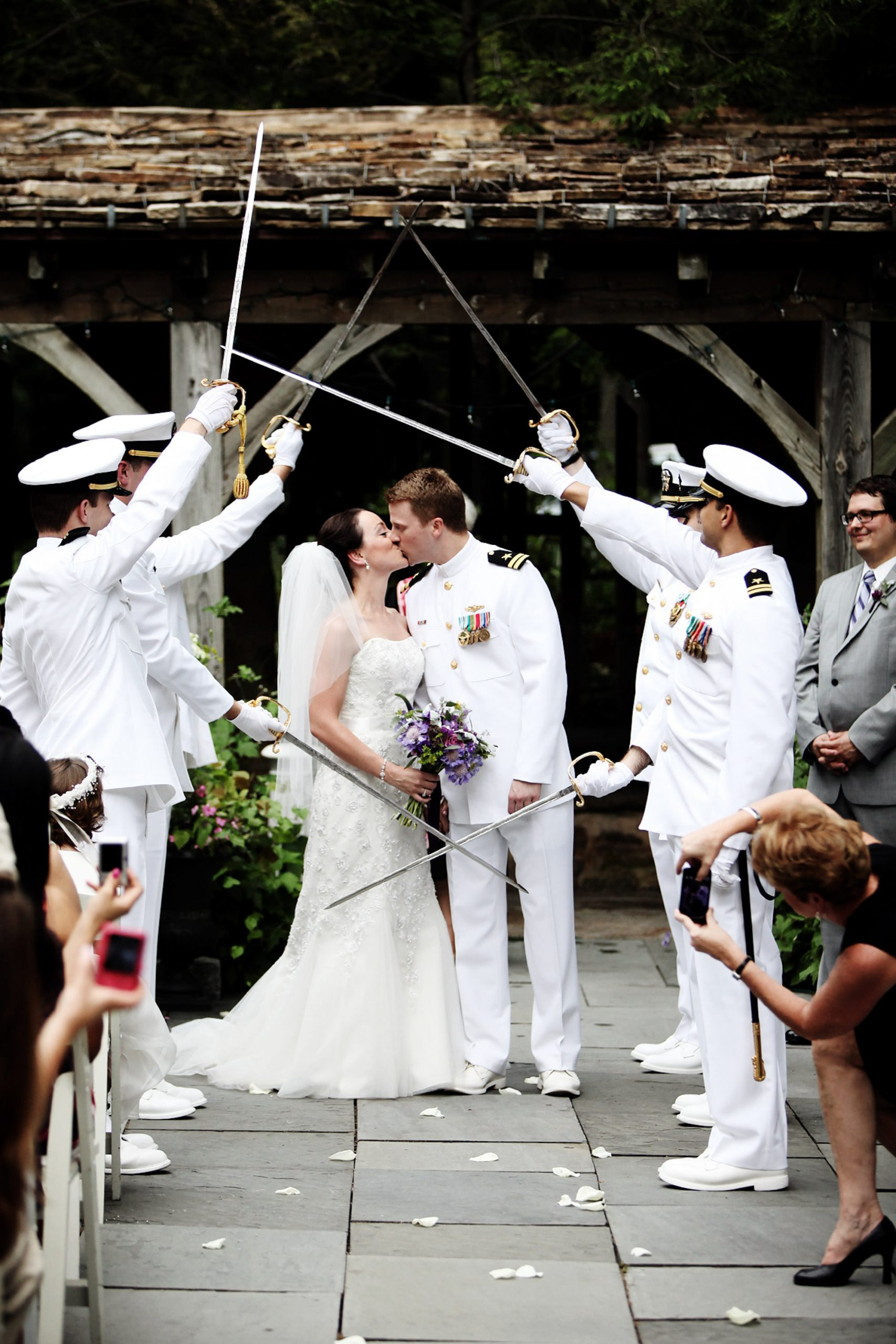 Cloisters Castle Wedding  I  The bride and groom kiss under a sword arch  during the ceremony in Lutherville, MD.