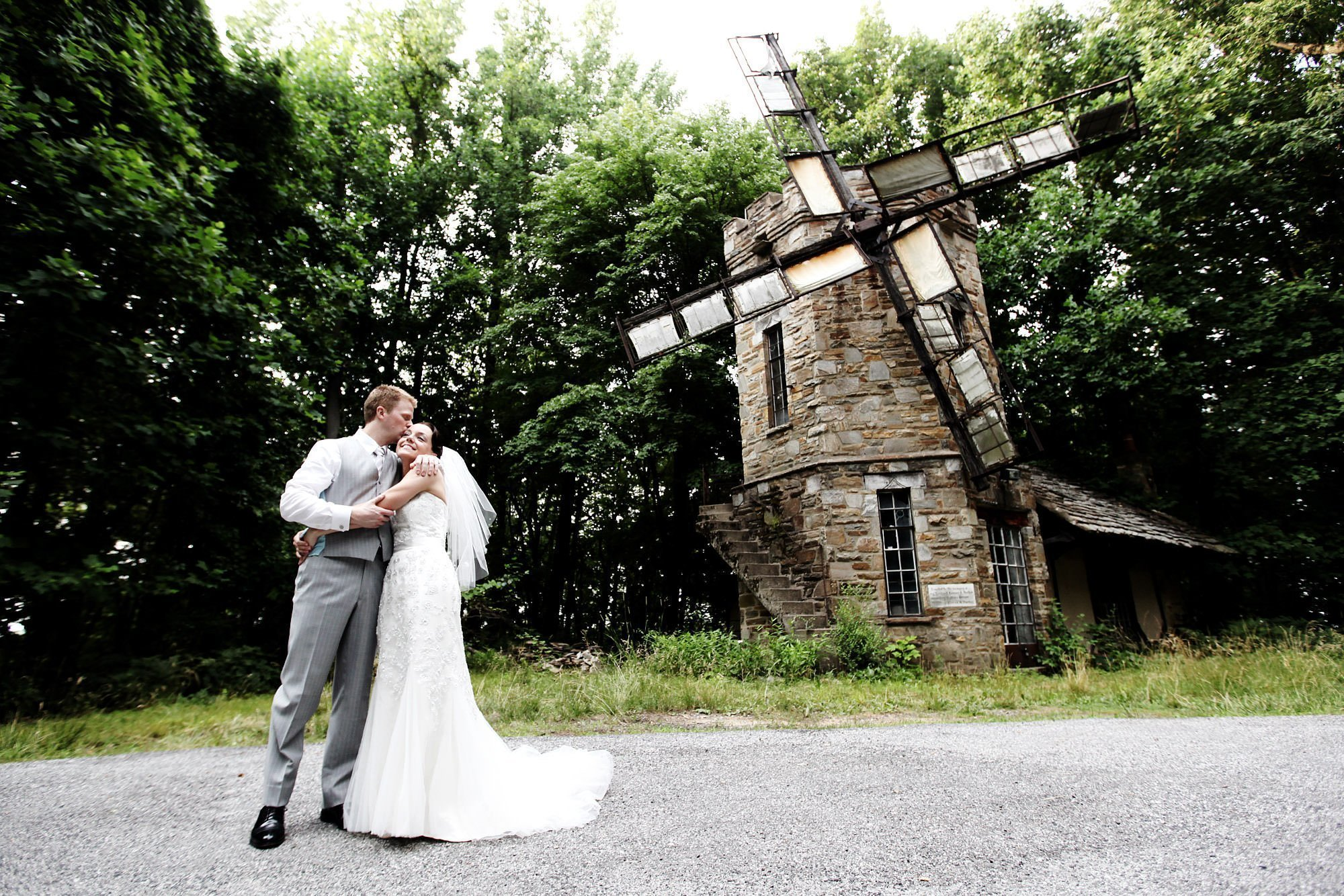 Cloisters Castle Wedding  I  The couple kiss by an old windmill in Lutherville, MD.