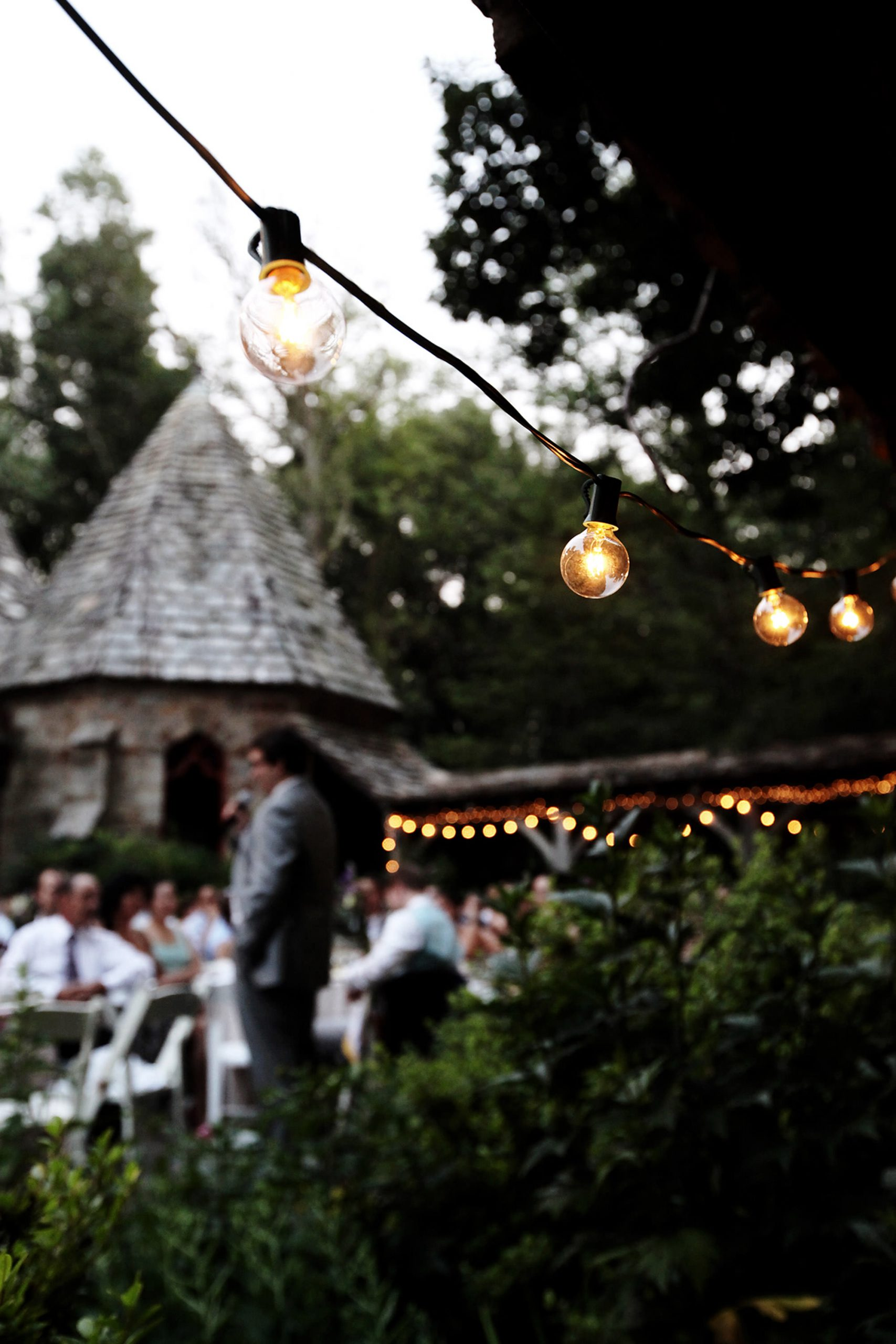Cloisters Castle Wedding  I  Twinkle lights hang as guests give toasts during the outdoor wedding reception in Lutherville, MD.