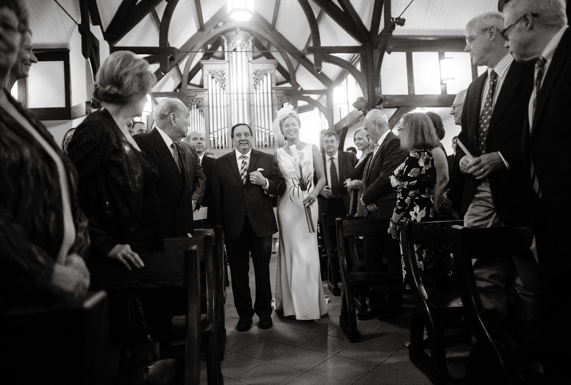 The bride walks down the aisle with her father at St. Alban's Church.