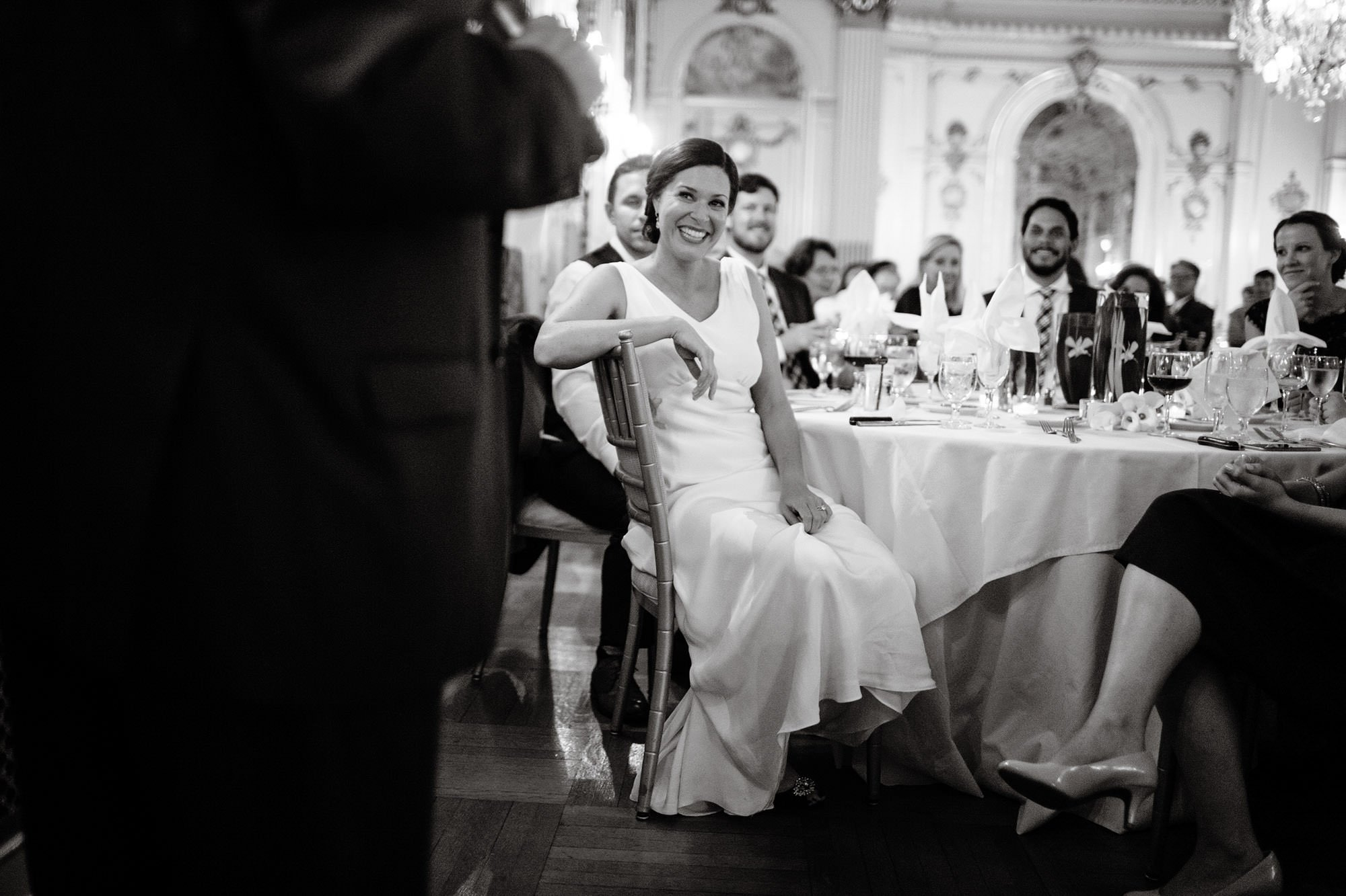 The bride listens to toasts during the wedding reception.
