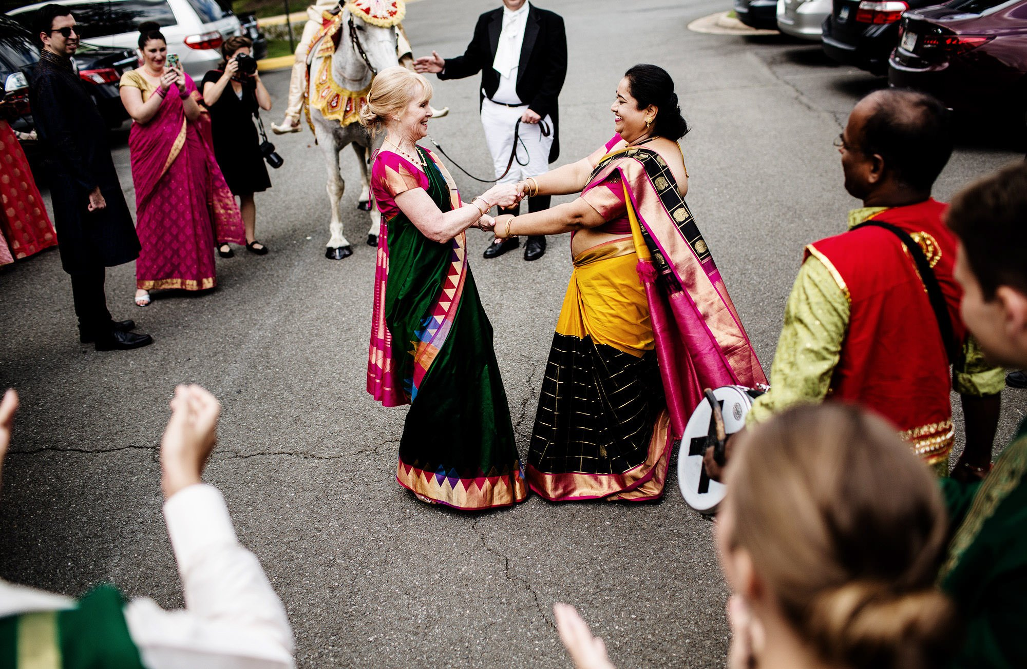 Guests dance in the parking lot during the Baraat outside of Foxchase Manor in Manassas, VA.