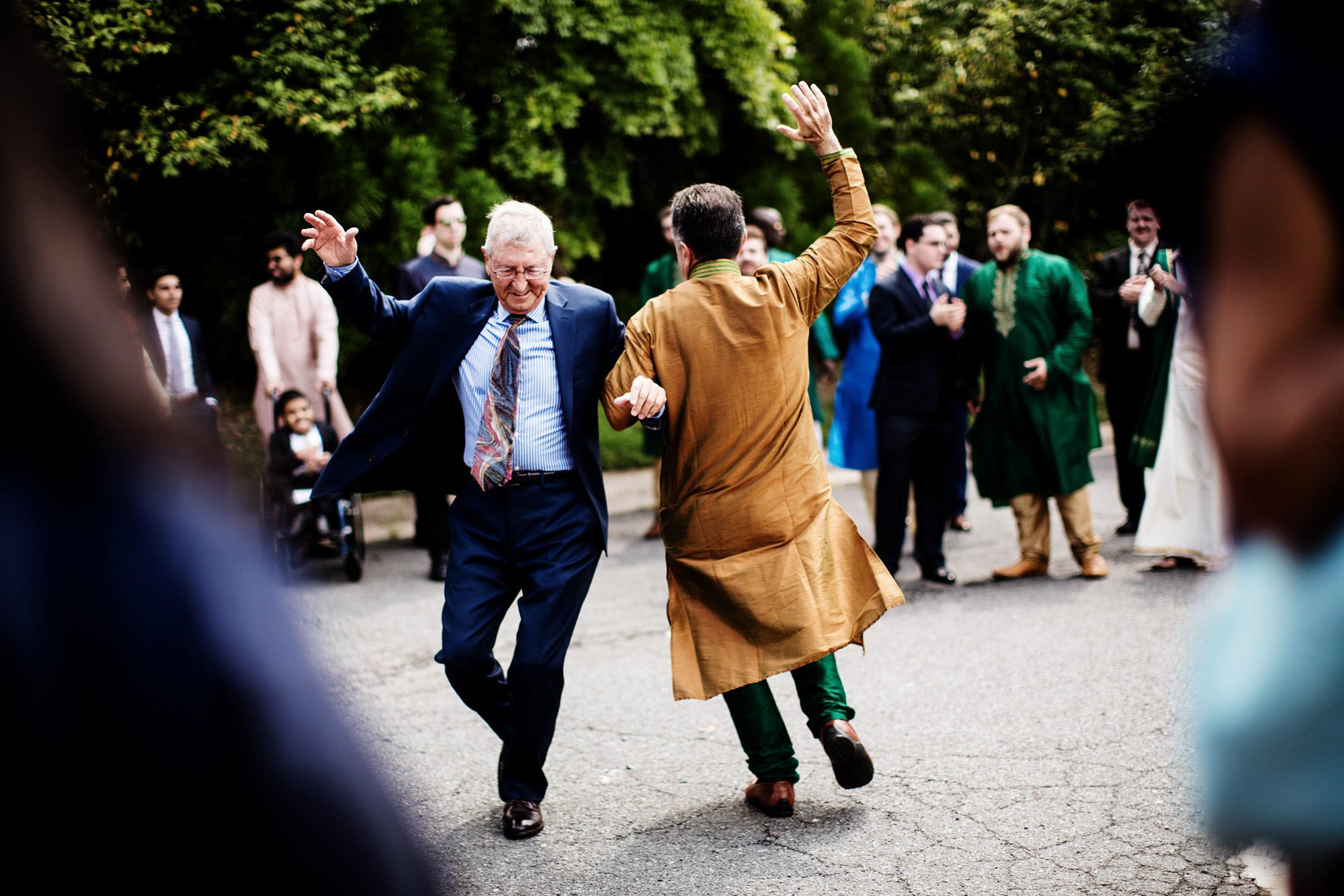 Guests dance in the parking lot during the Baraat outside of this Foxchase Manor wedding in Manassas, VA.
