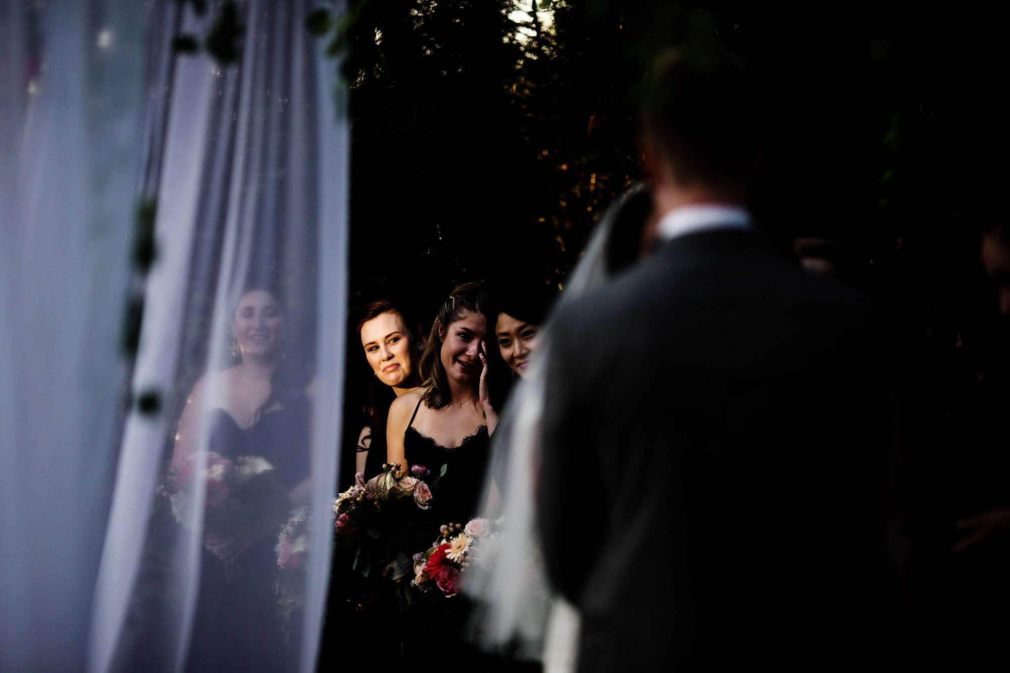 Bridesmaids watch the bride and groom during this outdoor ceremony at Foxchase Manor.