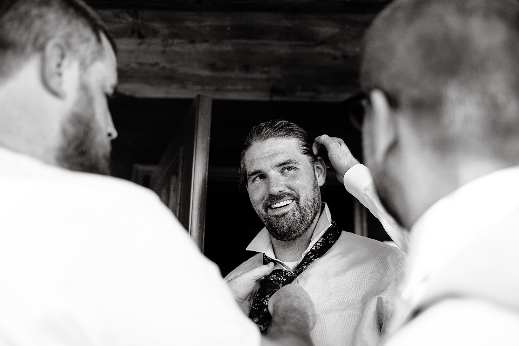 The groom gets ready prior to the ceremony at Hulbert Outdoor Center.
