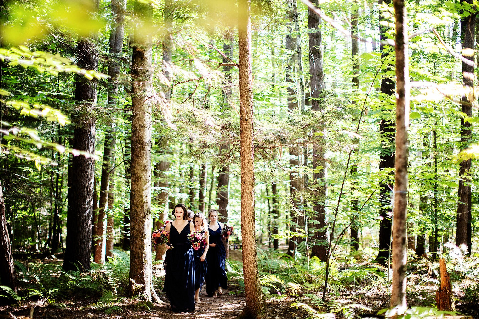 Bridesmaids walk through the trees prior to the wedding reception at Hulbert Outdoor Center.