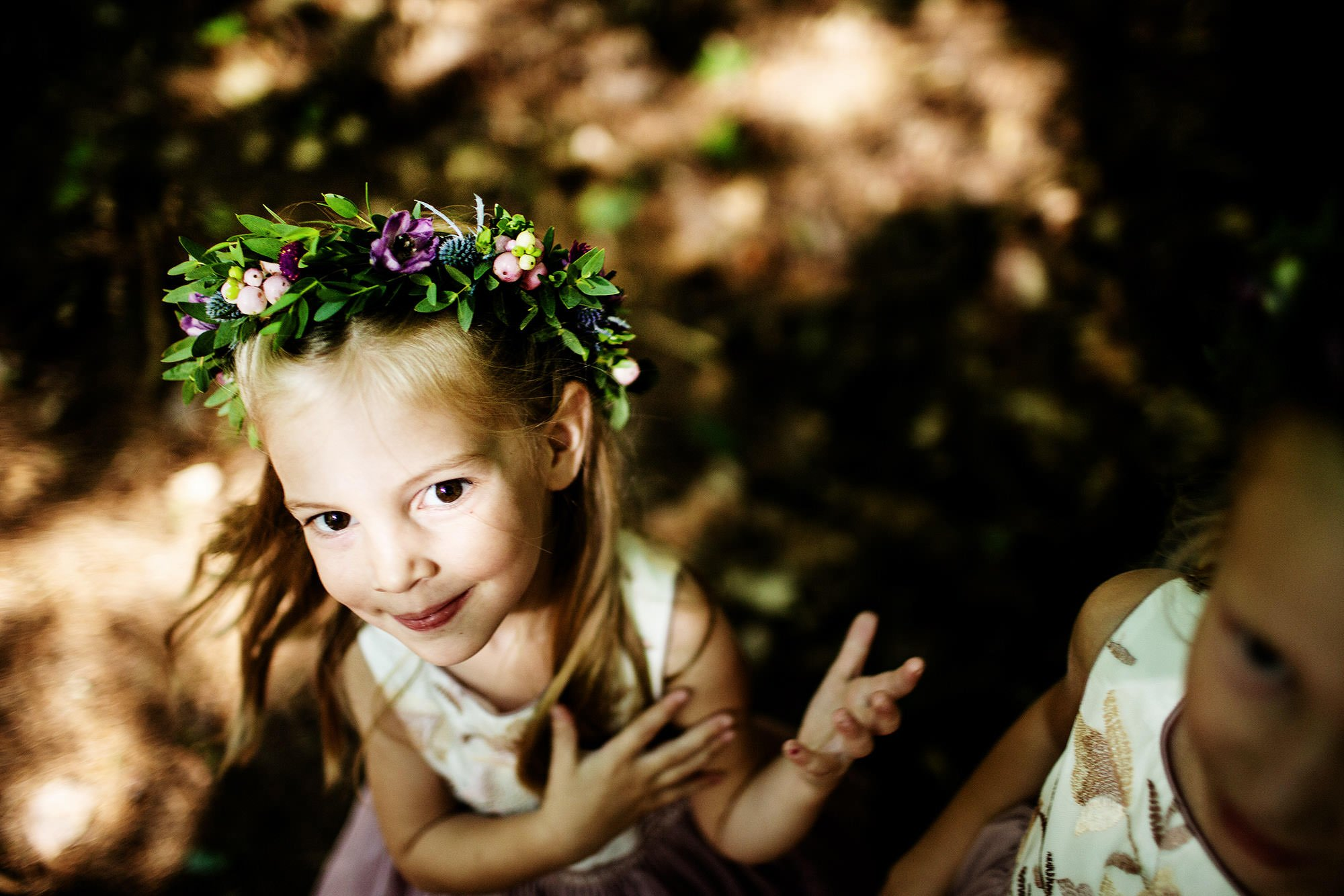 A flower girl shows off her flowers at Hulbert Outdoor Center prior to the wedding ceremony.