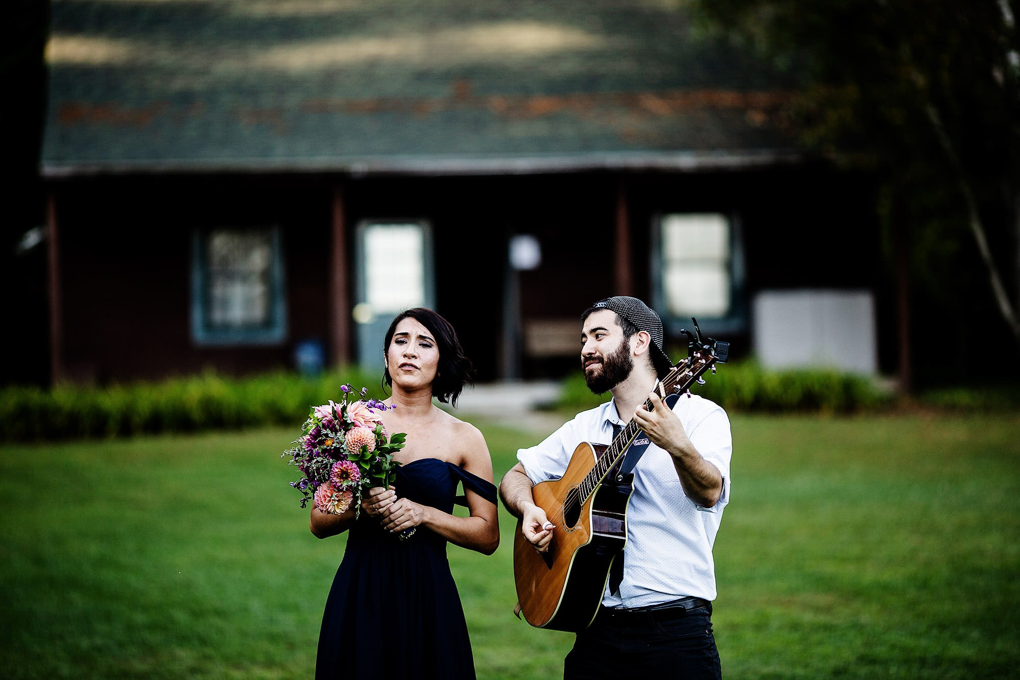 Guests play music and sing during cocktail hour of this Hulbert Outdoor Center wedding.
