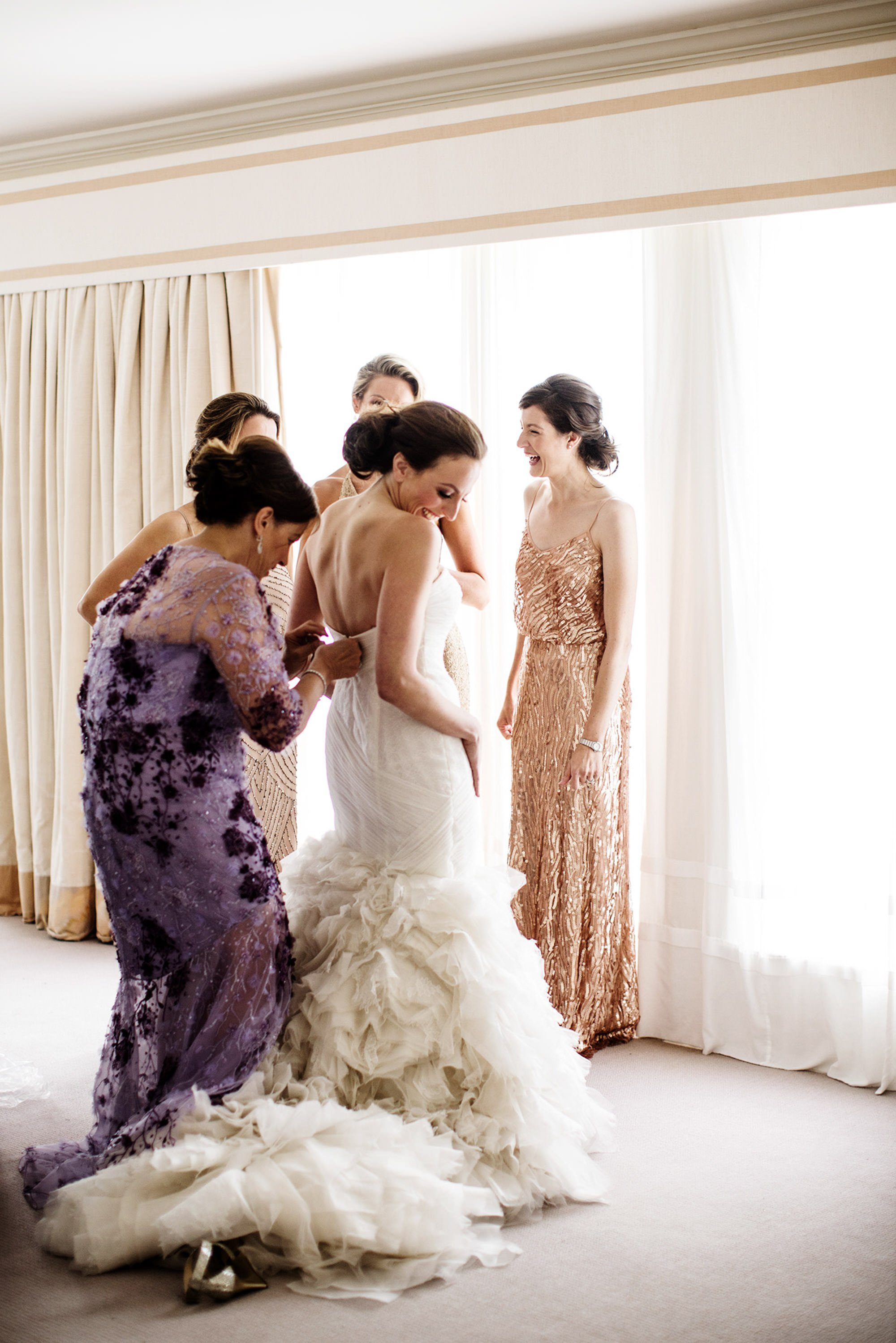 The mother of the bride helps put on her daughter's wedding dress.