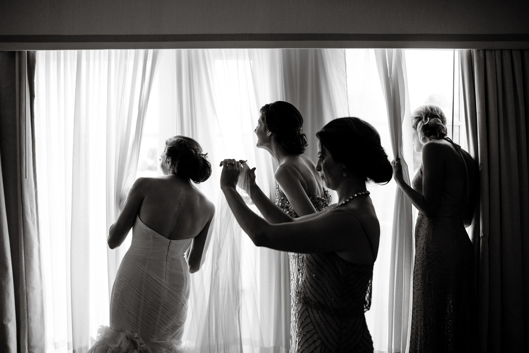 The bridal party watches while guests arrive for the wedding ceremony.