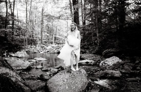 The bride smiles while standing on a rock in Mill Brook prior to her Mad River Barn wedding in Waitsfield, VT.