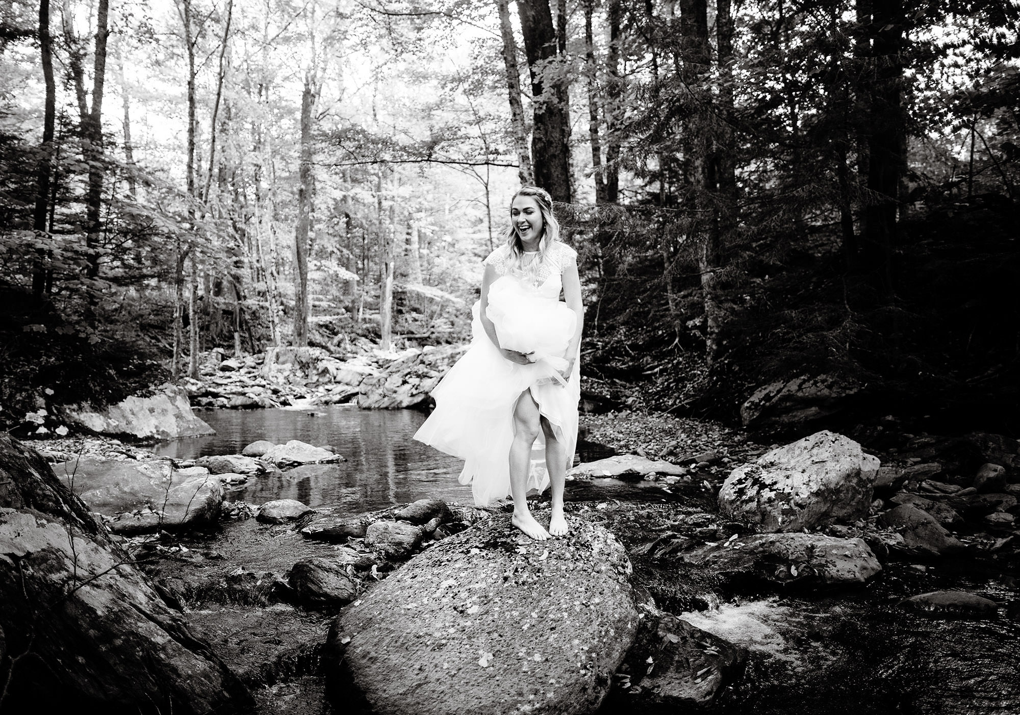 The bride smiles while standing on a rock in Mill Brook prior to her wedding at Mad River Barn in Waitsfield, VT.