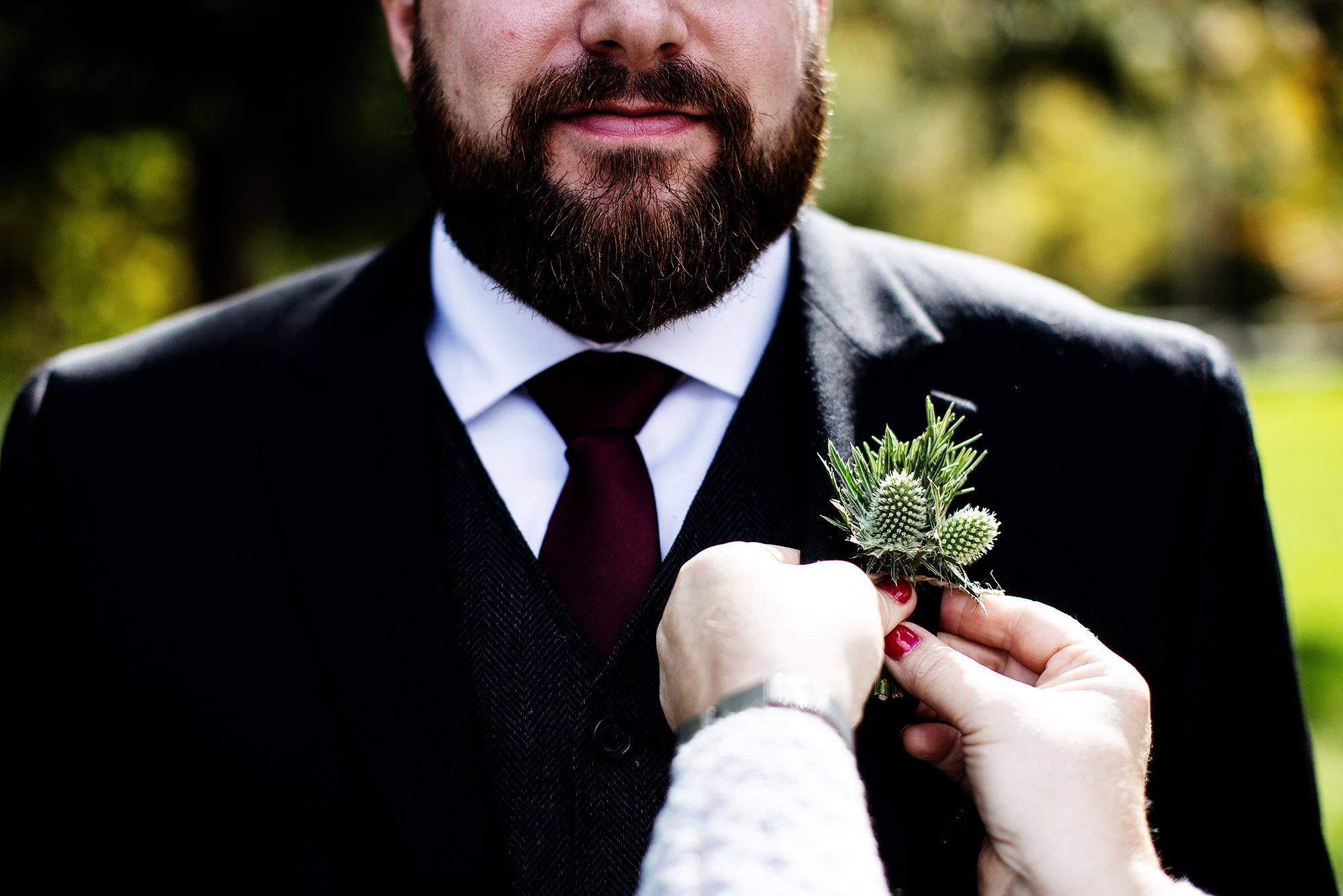 The groom puts on his Boutonniere prior to the ceremony at Mad River Barn.