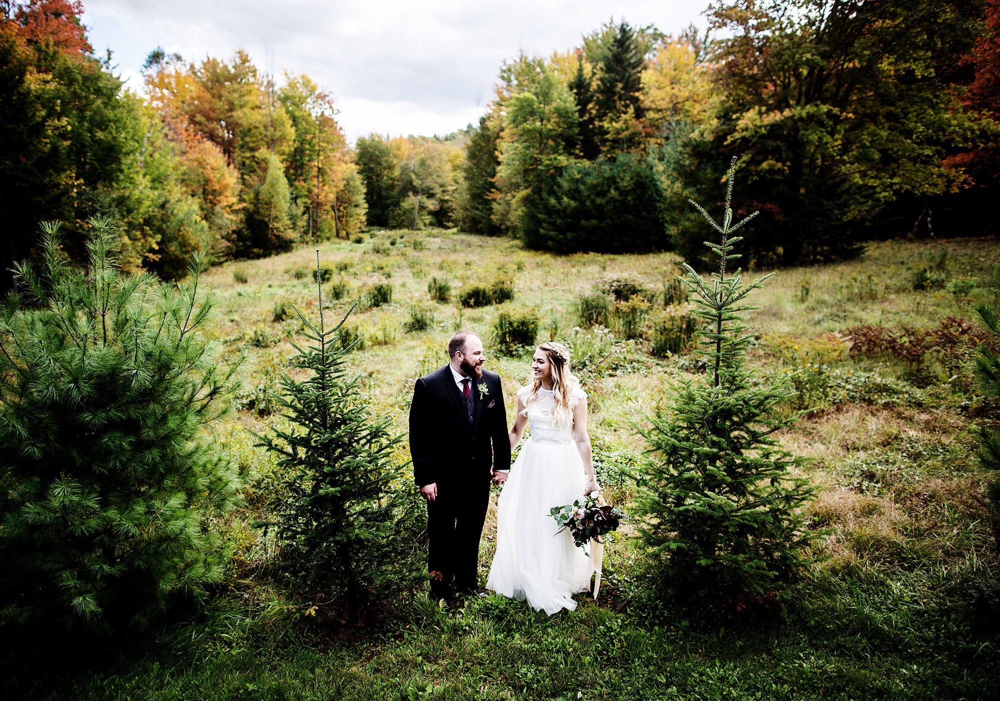 The bride and groom pose for a portrait during their Mad River Barn Wedding in Waitsfield, VT.