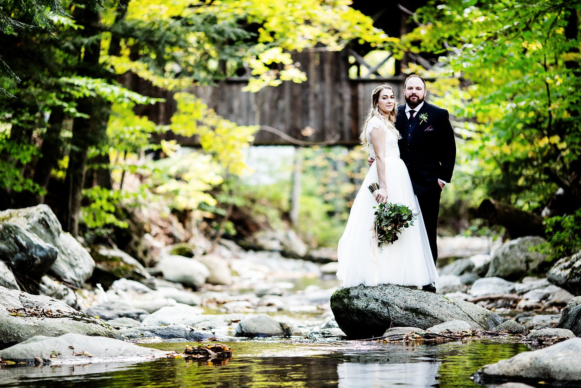 The bride and groom pose for a portrait while standing on a rock in Mill Brook.