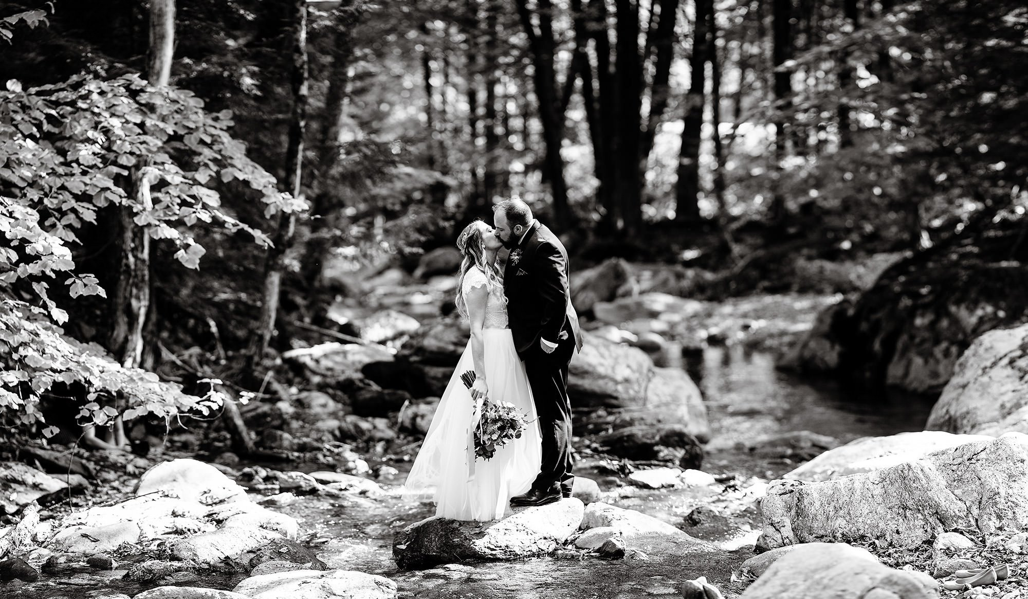 The bride and groom kiss while standing on a rock in Mill Brook.
