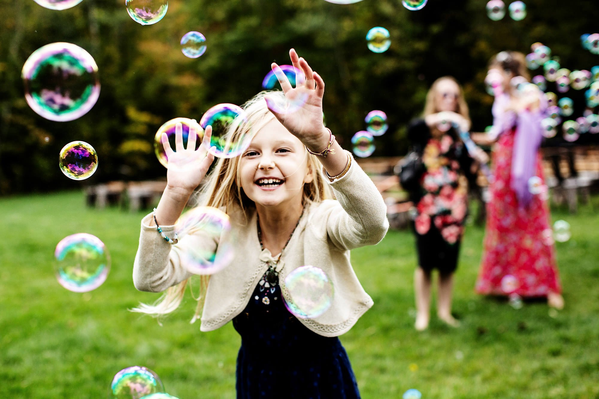 A girl runs through bubbles during cocktail hour during this Mad River Barn wedding.
