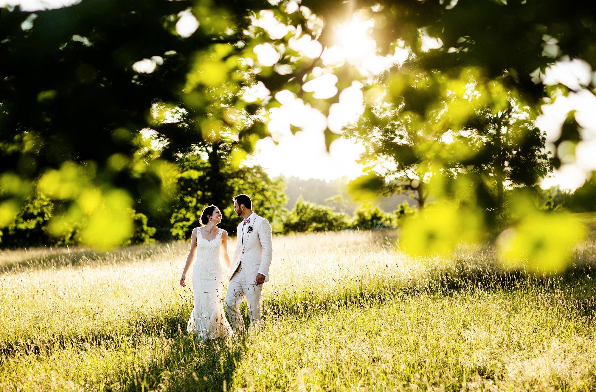 The bride and groom walk through a field during their Mesa Farm Wedding in Rutland, MA