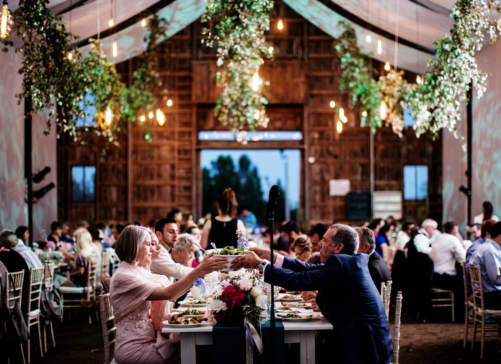 Guests eat dinner during their Mesa Farm Wedding.