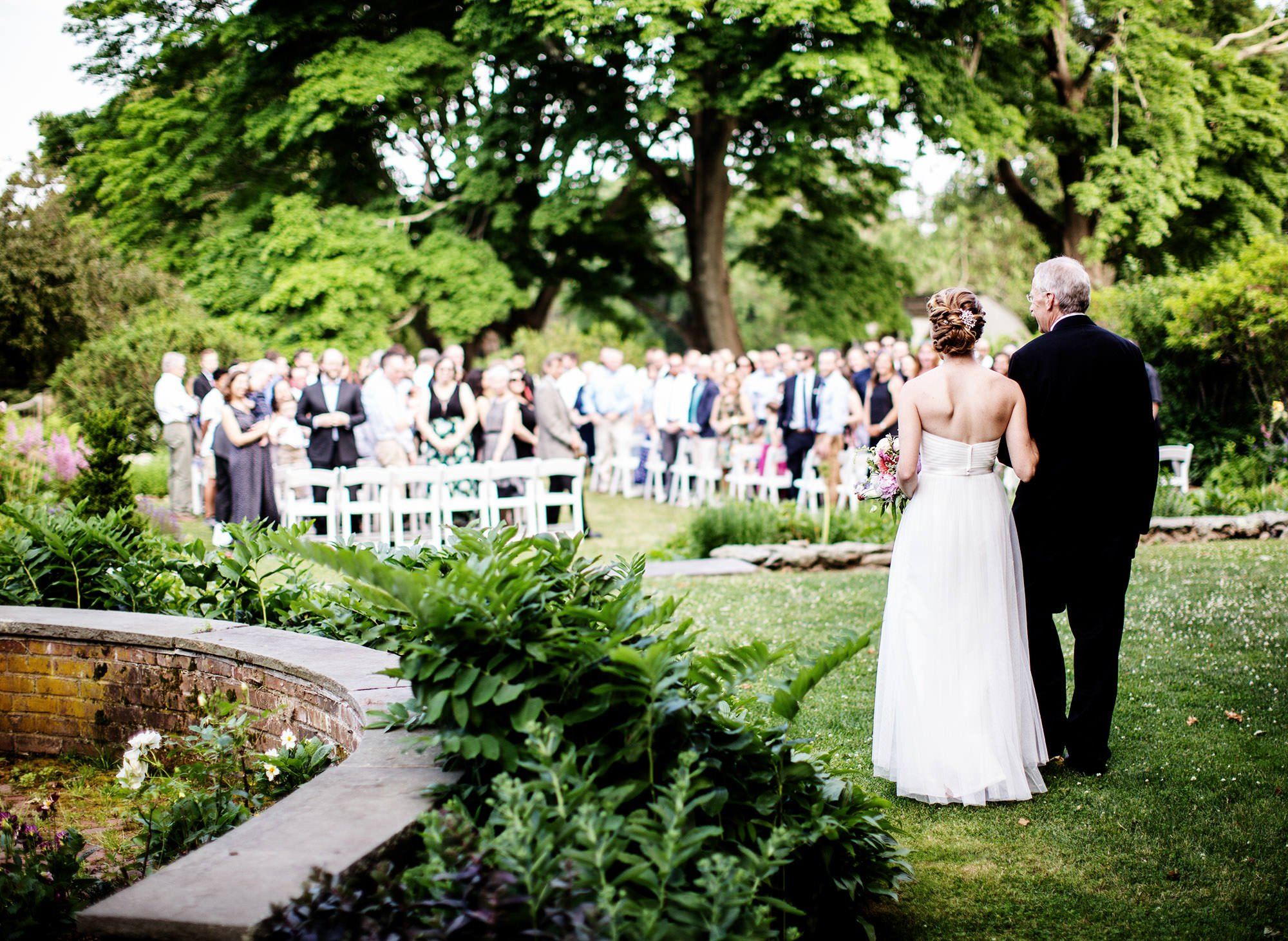 The bride and her father walk down the aisle for the wedding ceremony at Mount Hope Farm.
