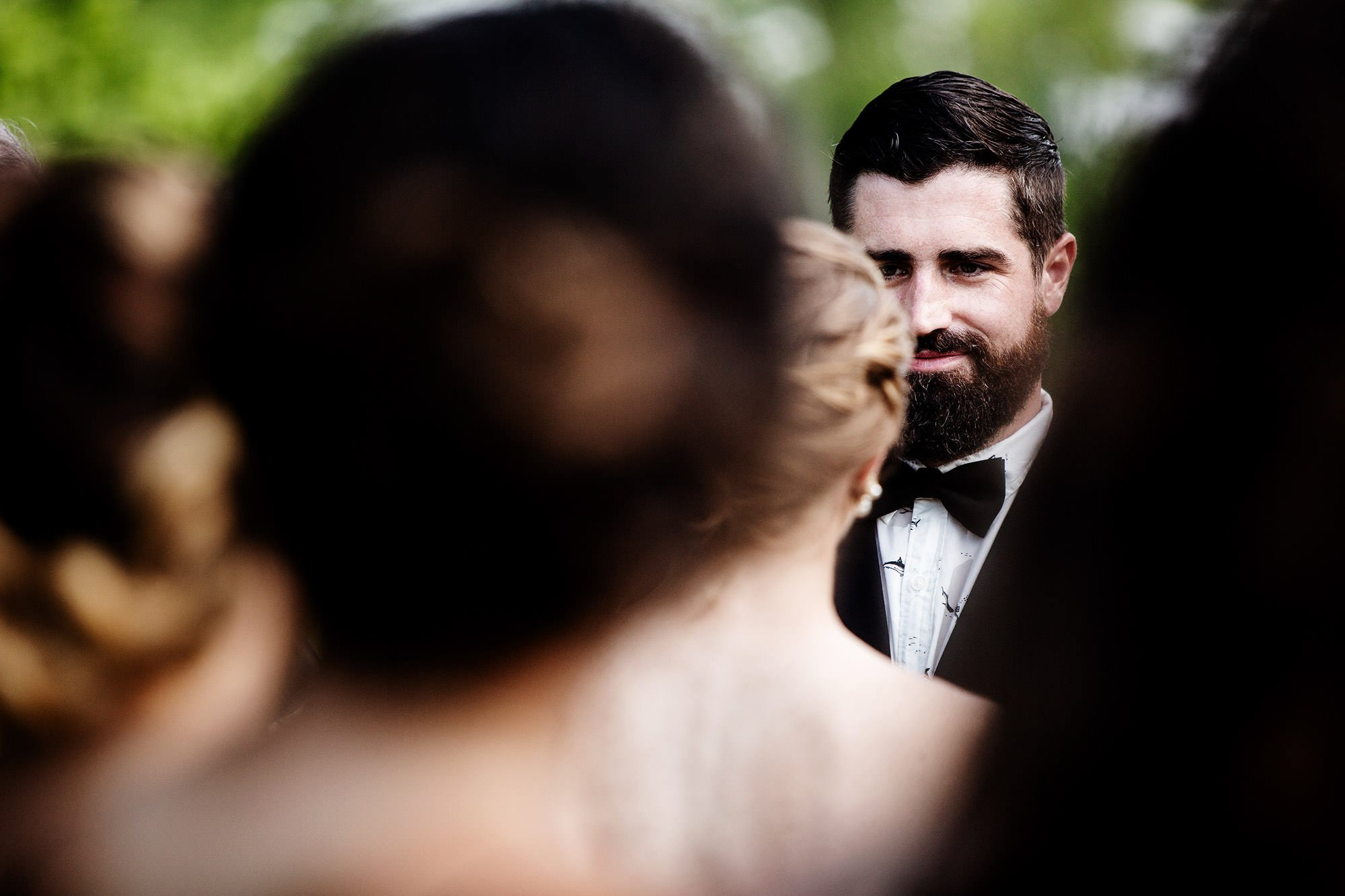 The groom looks at his bride during the wedding ceremony at Mount Hope Farm.