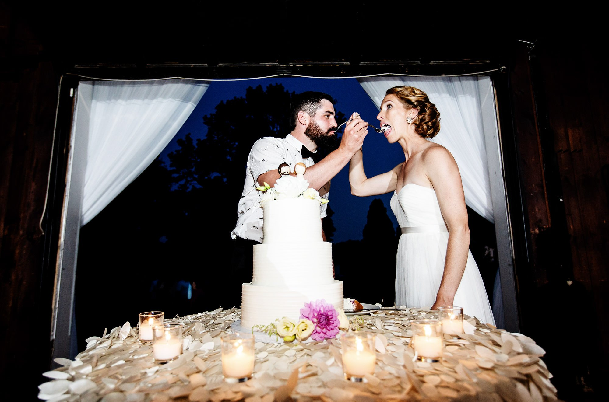 The Bride and Groom cut the cake during their reception at Mount Hope Farm.