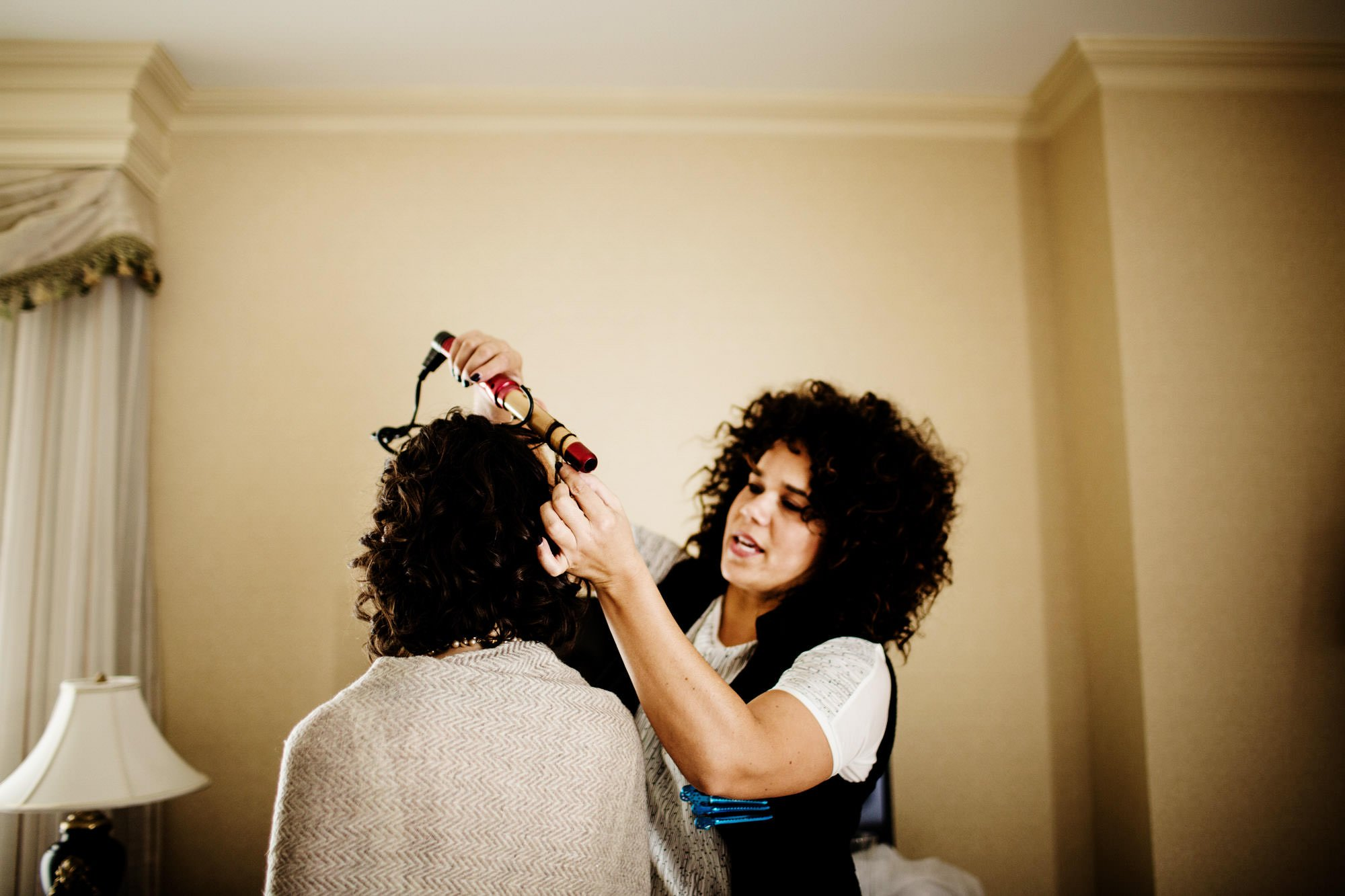The bride gets her hair done prior to her ceremony.