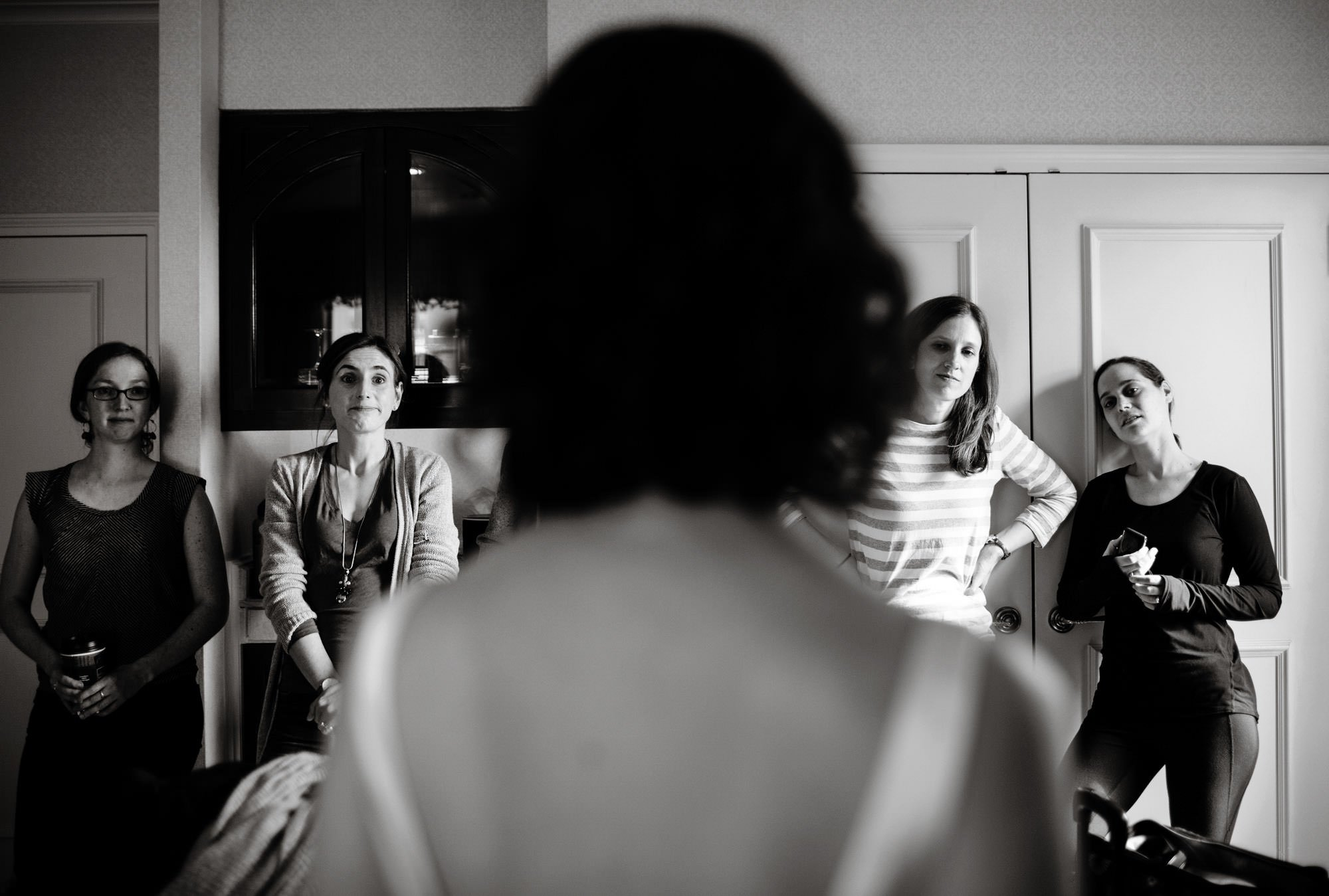 The bride stands before her bridesmaids while wearing her wedding dress.