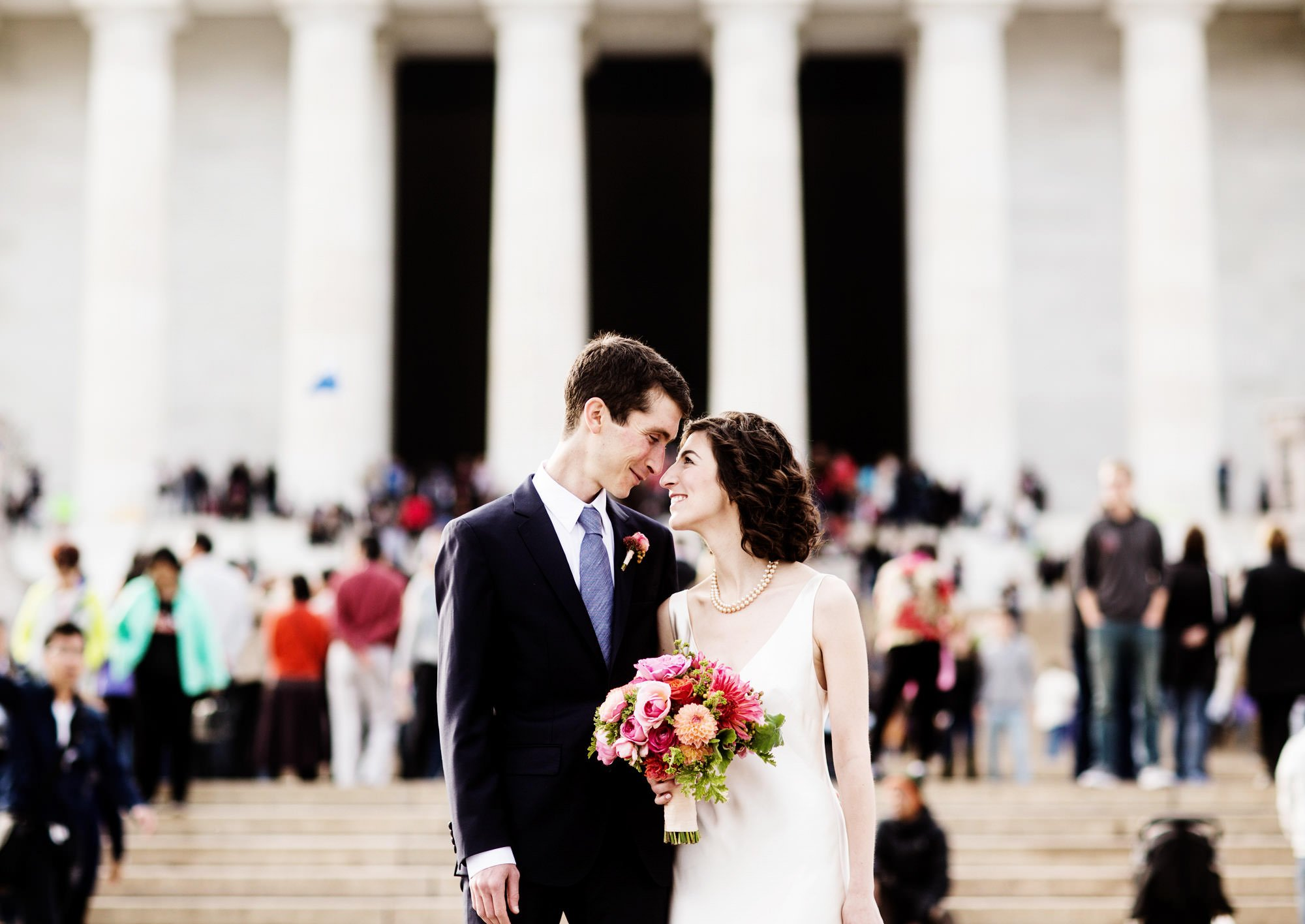 The bride and groom pose for a portrait in front of the Lincoln Memorial.