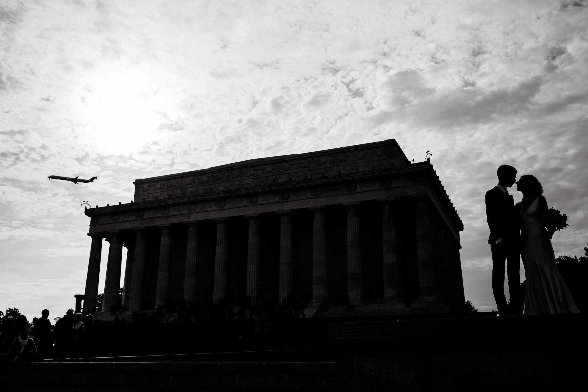 The bride and groom are silhouetted next to the Lincoln Memorial.