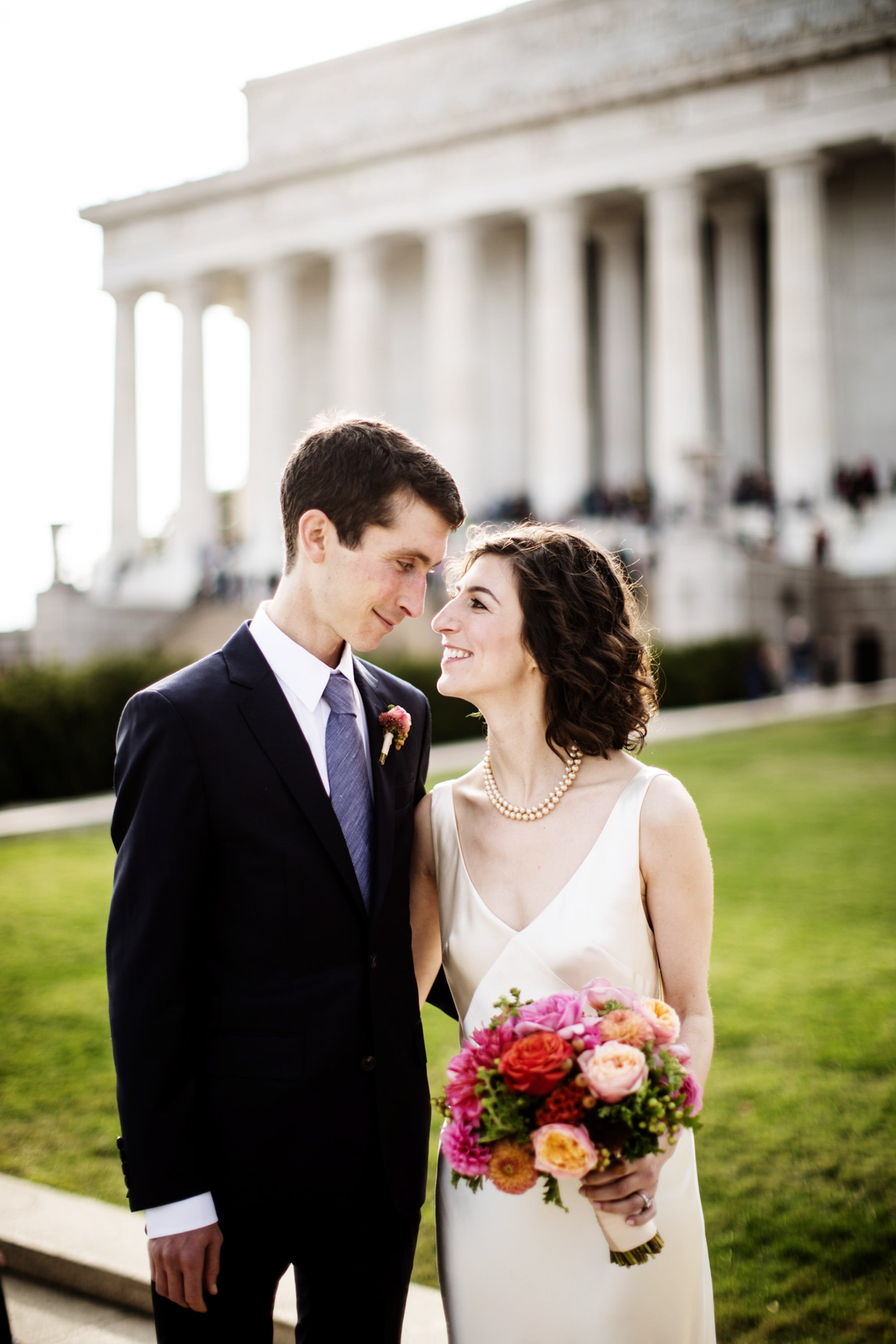The bride and groom pose for a portrait in front of the Lincoln Memorial in Washington, DC.