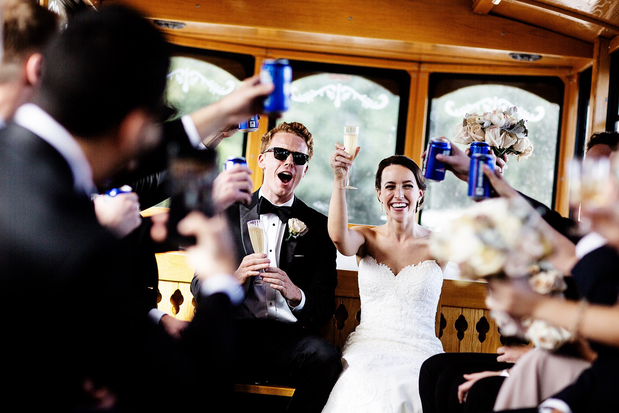 The wedding party cheers on board a trolley following the ceremony on Cape Cod.