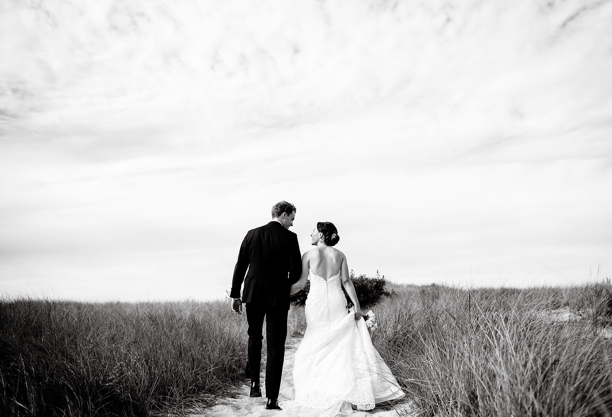 The couple walks to the beach at Crosby Landing Beach prior to their Ocean Edge Resort reception.