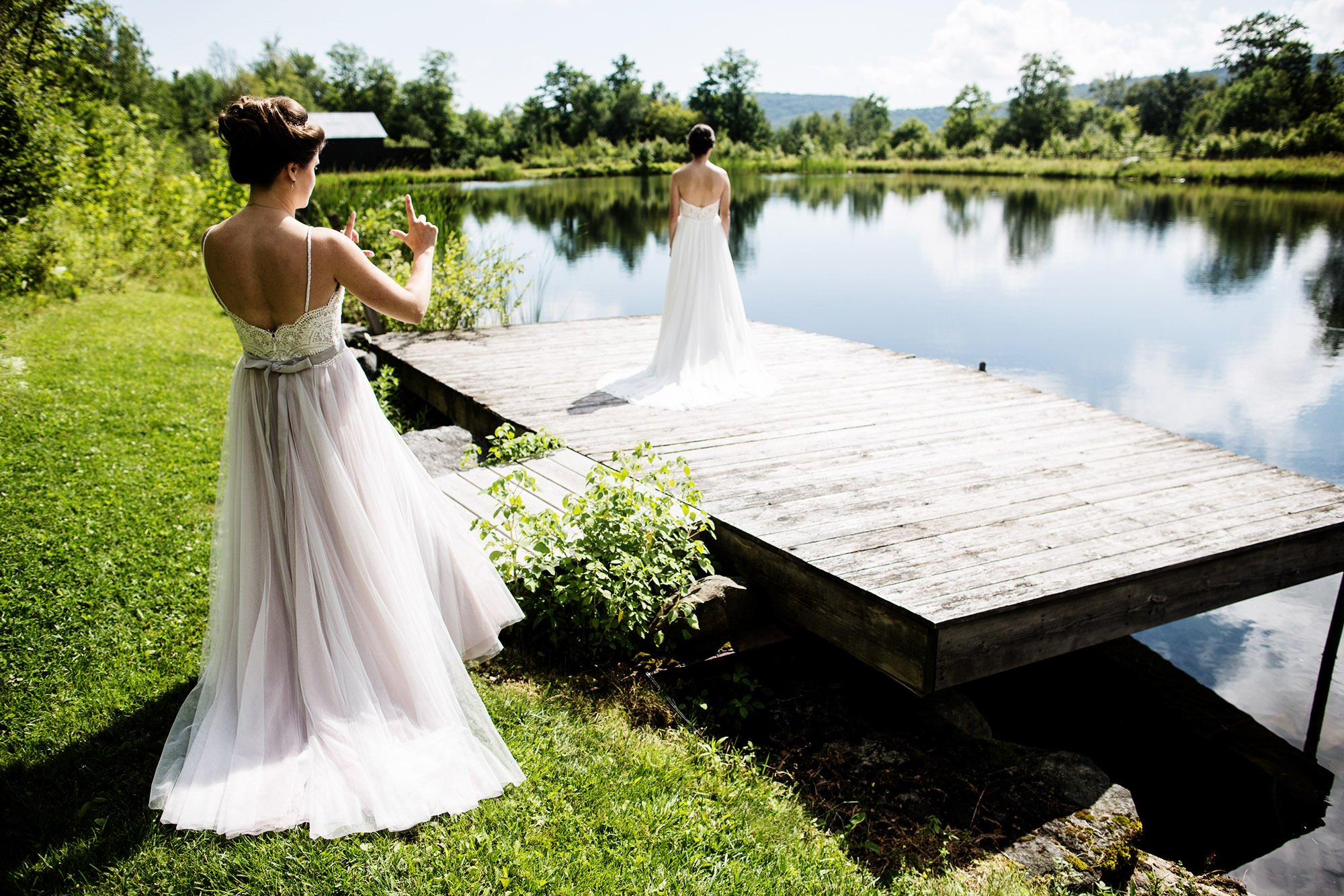 The brides share their first look on the dock of The Ponds at Bolton Valley