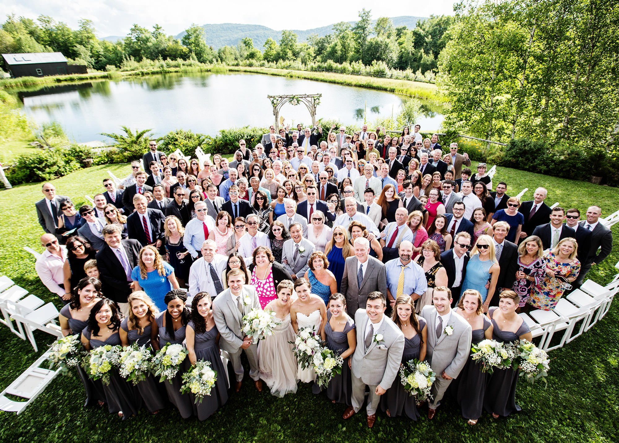 An overall portrait of the wedding party and their guests at the Ponds.