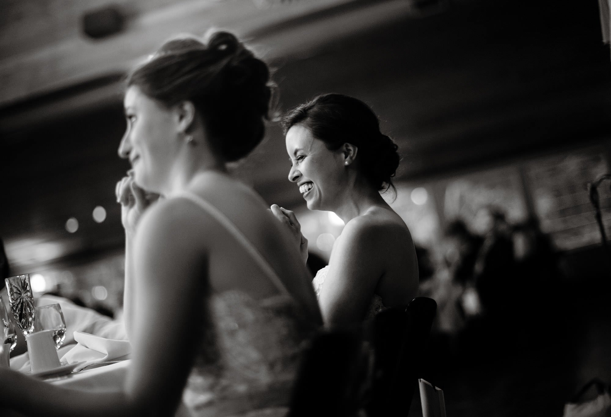 The brides enjoy the toasts during the wedding reception.