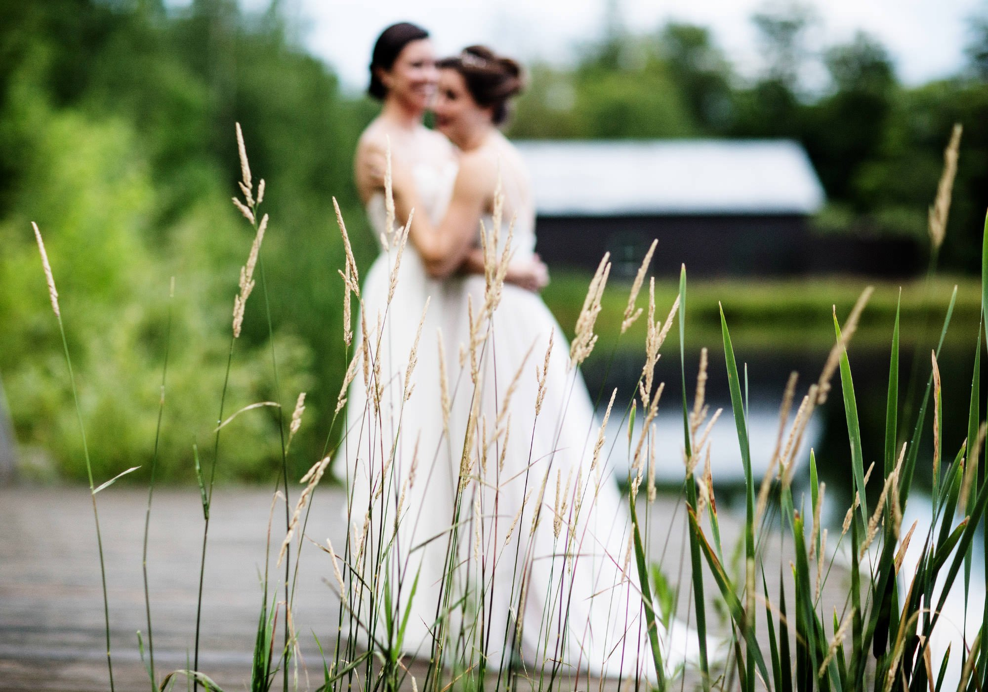 The brides share a moment on the dock at The Ponds at Bolton Valley.