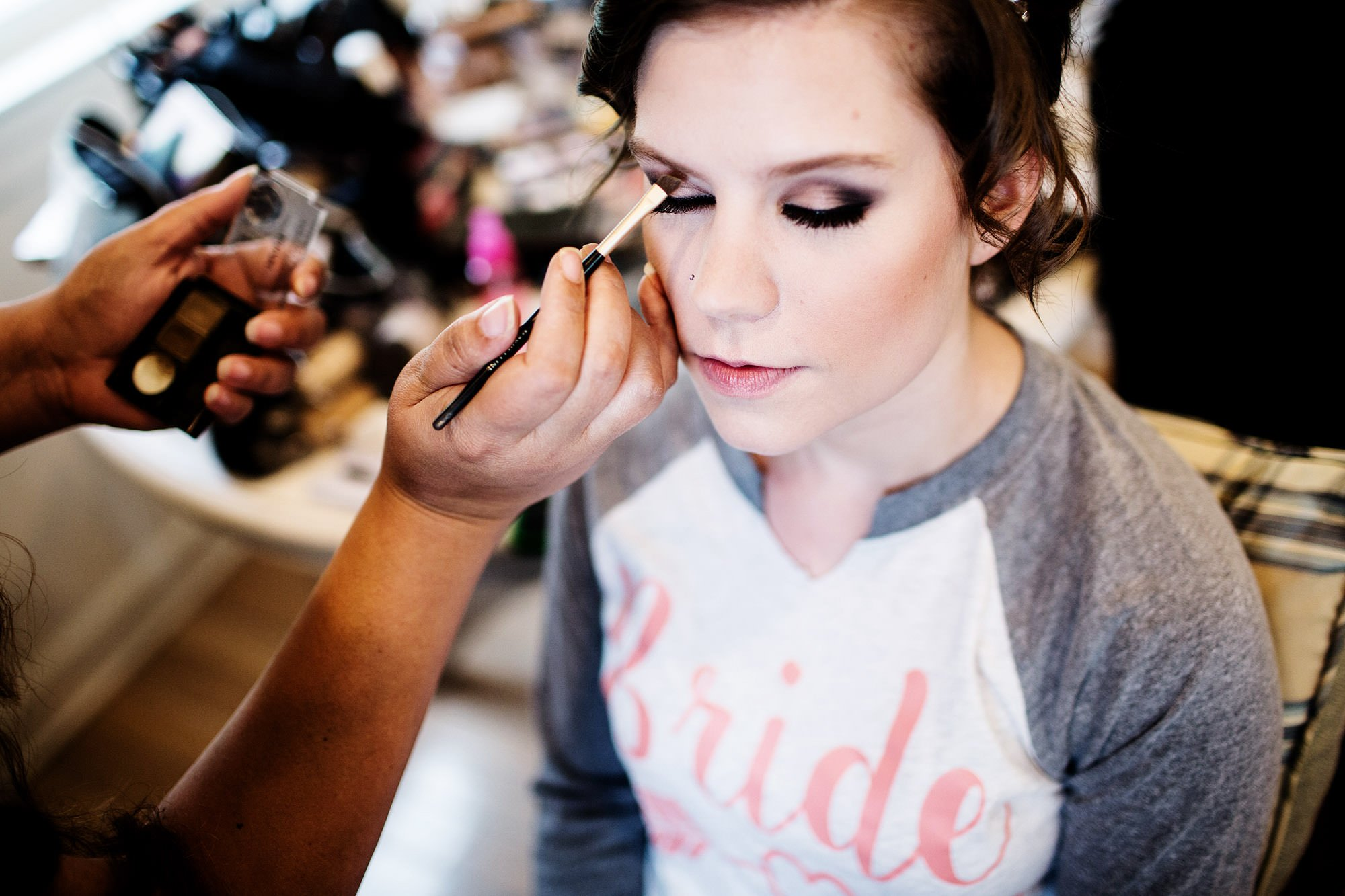 The bride has makeup applied prior to her ceremony at Oaks Waterfront Inn.