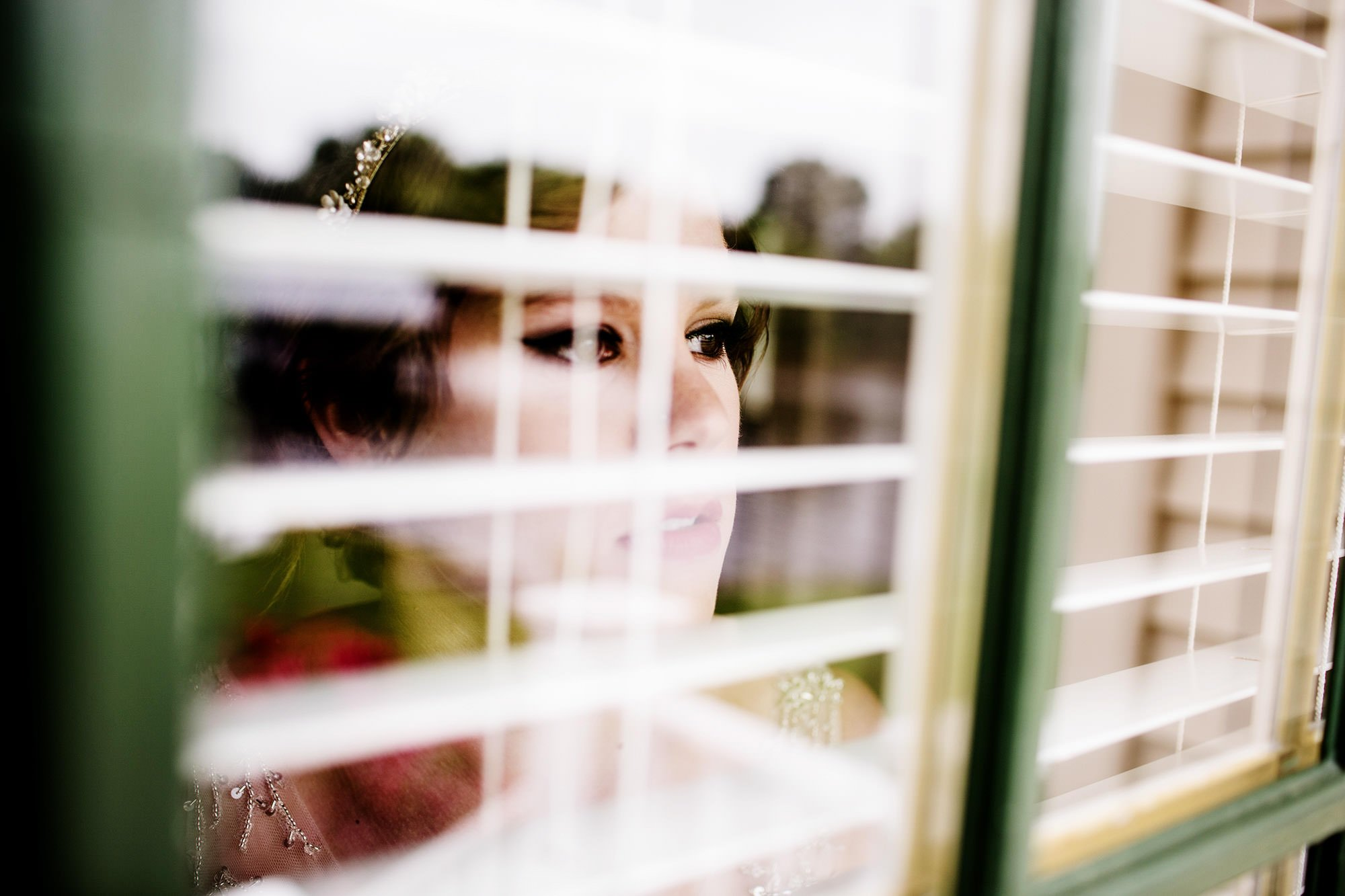 The bride keeps an eye on her guests as they arrive at for the wedding ceremony at Oaks Waterfront Inn.