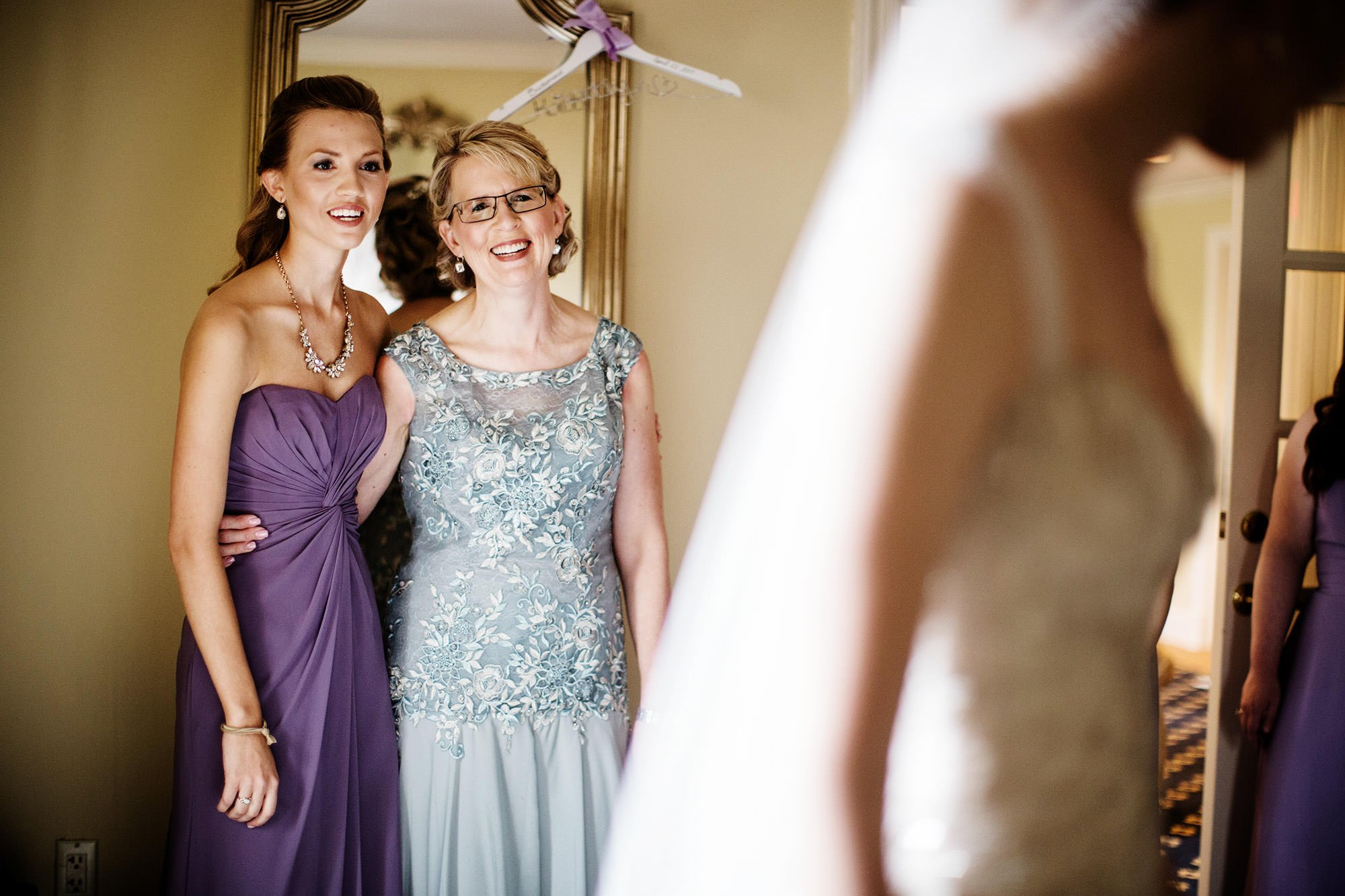 The mother of the bride looks at her daughter in her wedding dress.