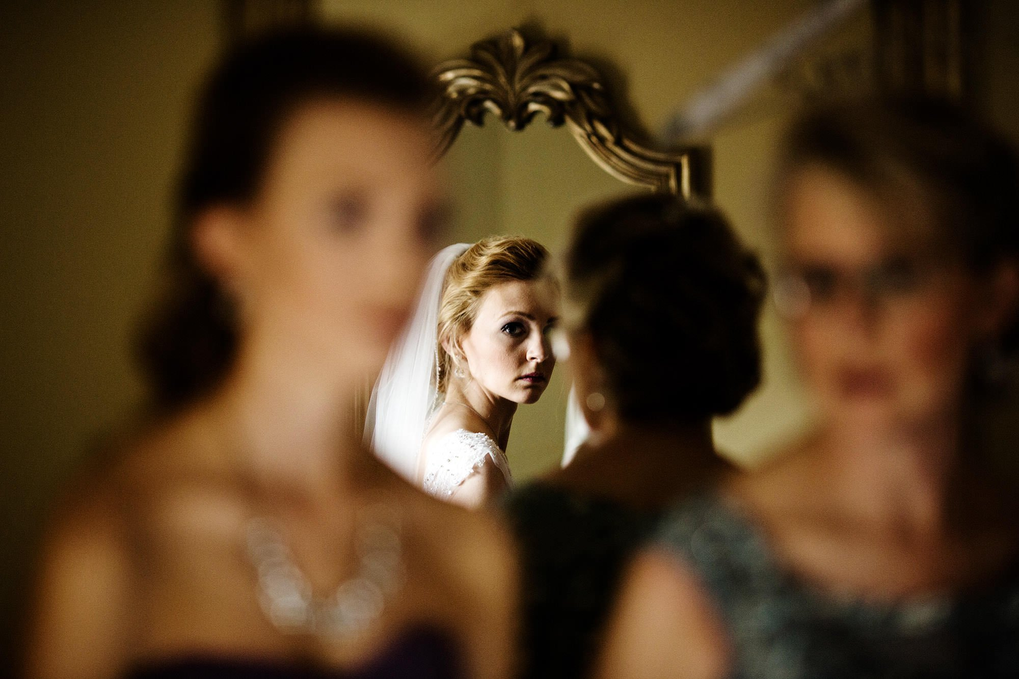 The bride looks in the mirror prior to the ceremony.