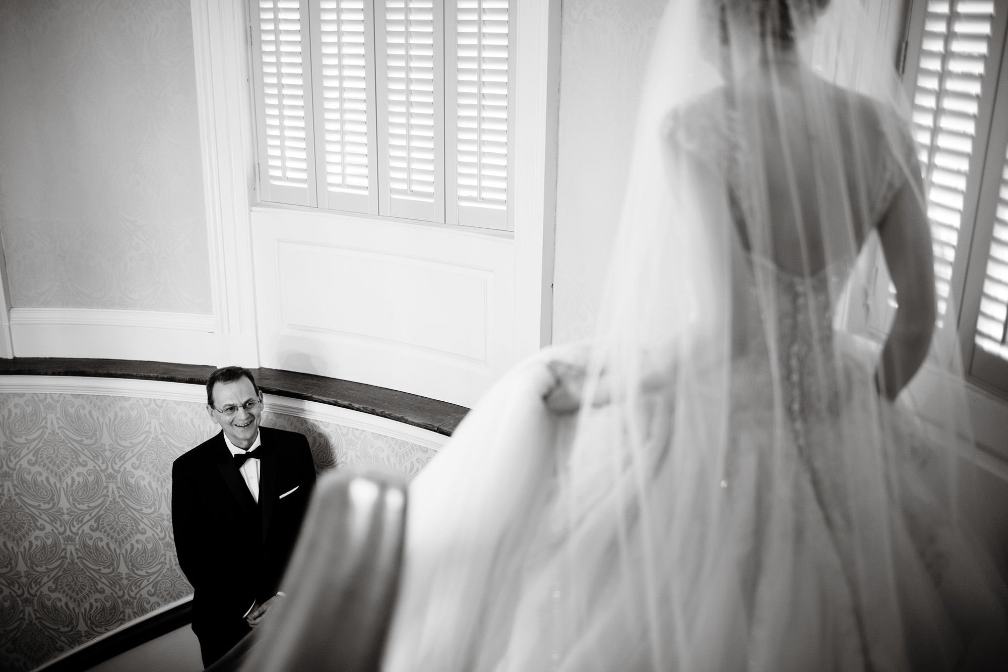 The father of the bride sees his daughter in the stairwell at this Tidewater Inn wedding.
