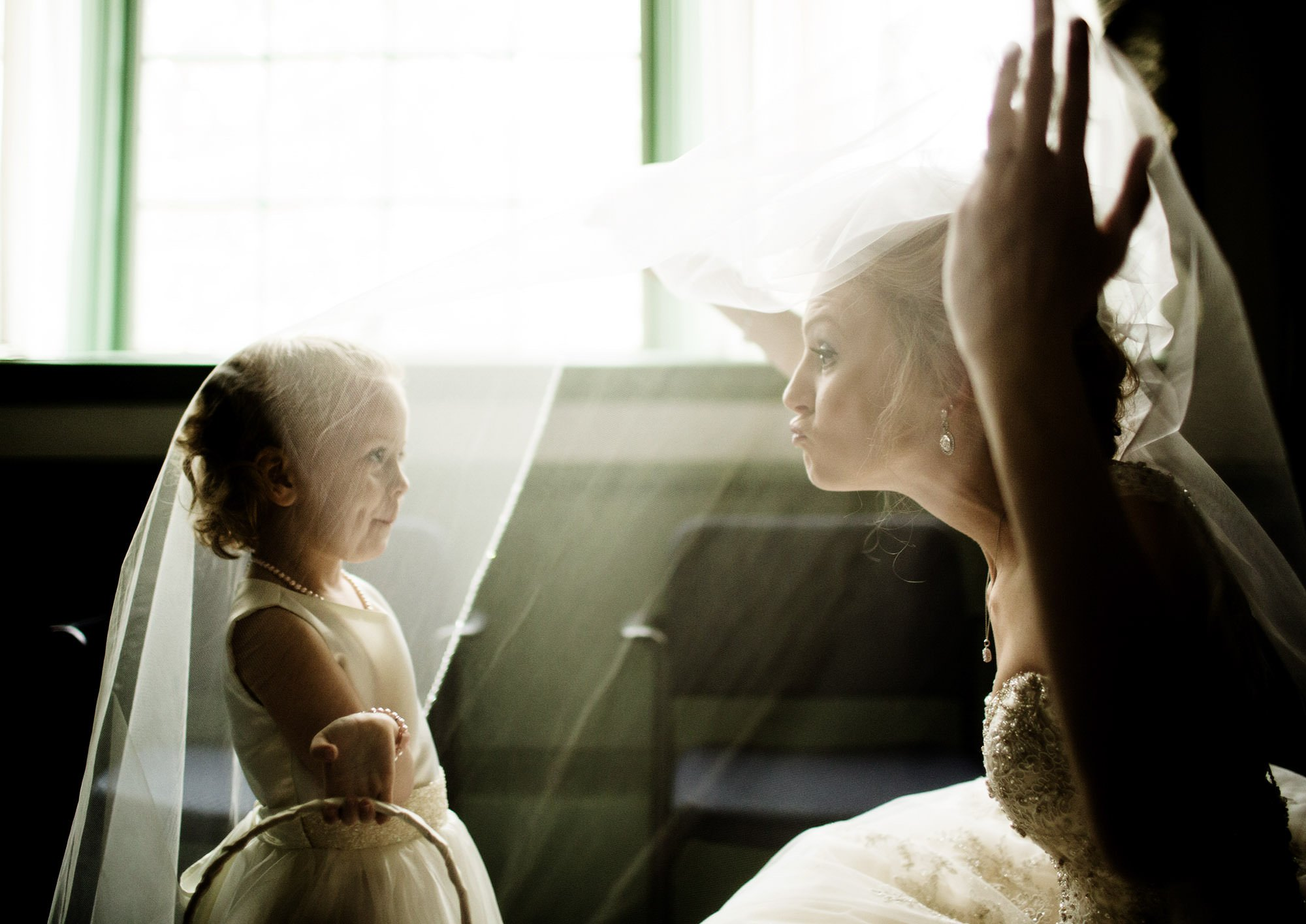 The bride shares a silly moment with her Flower Girl.