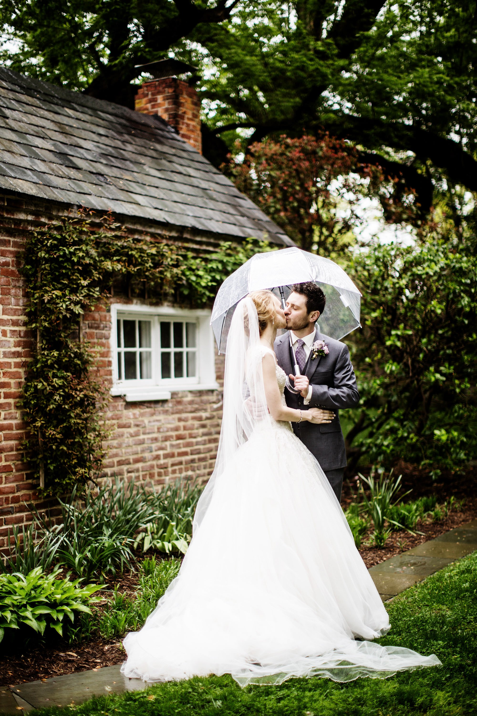 The bride and groom pose for a portrait in the rain in the garden across the street from the Tidewater Inn.
