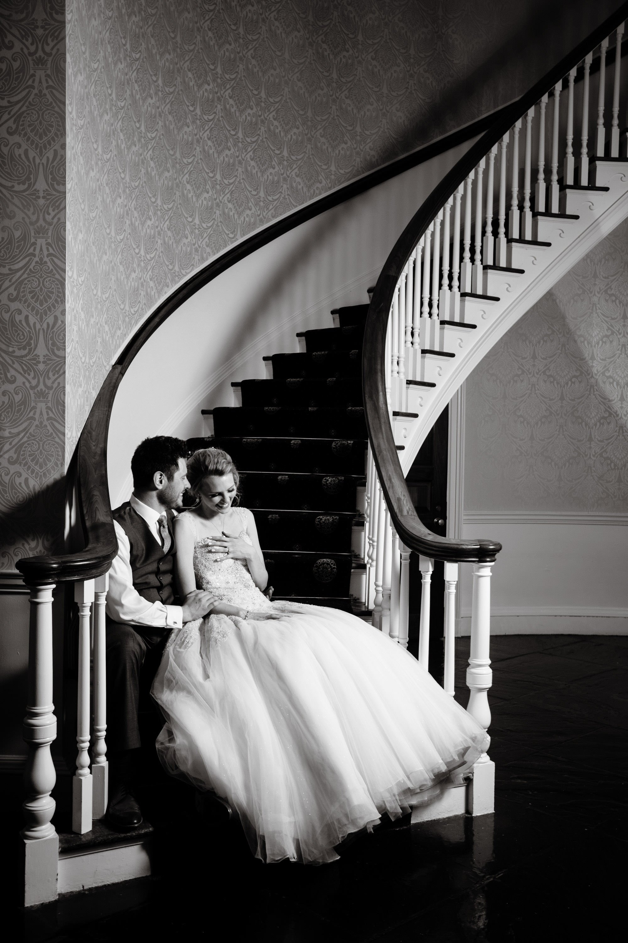 The bride and groom pose for a portrait on the stairs of the Tidewater Inn during their wedding reception.