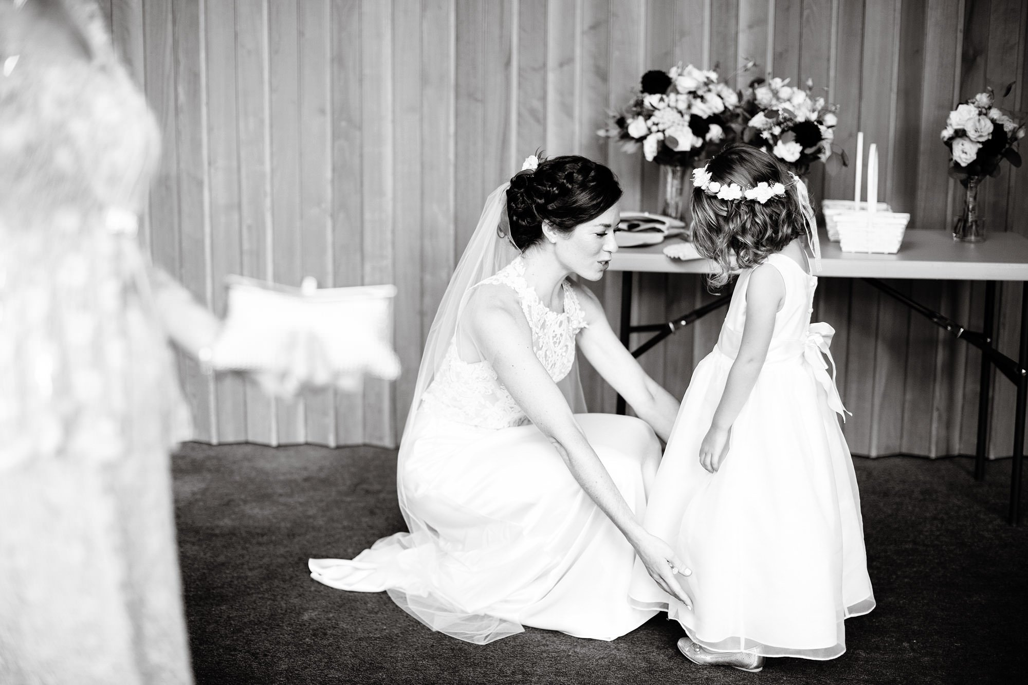 The bride looks at the dress of her flower girl prior to the Ceremony at Pilgrim Covenant Church in Lunenberg, MA