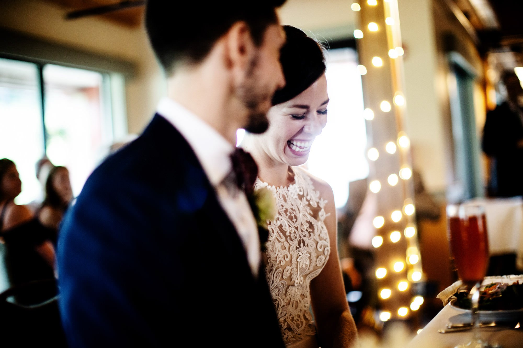 The bride and groom share a laugh during toasts at their ski lodge wedding at Wachusett Mountain.