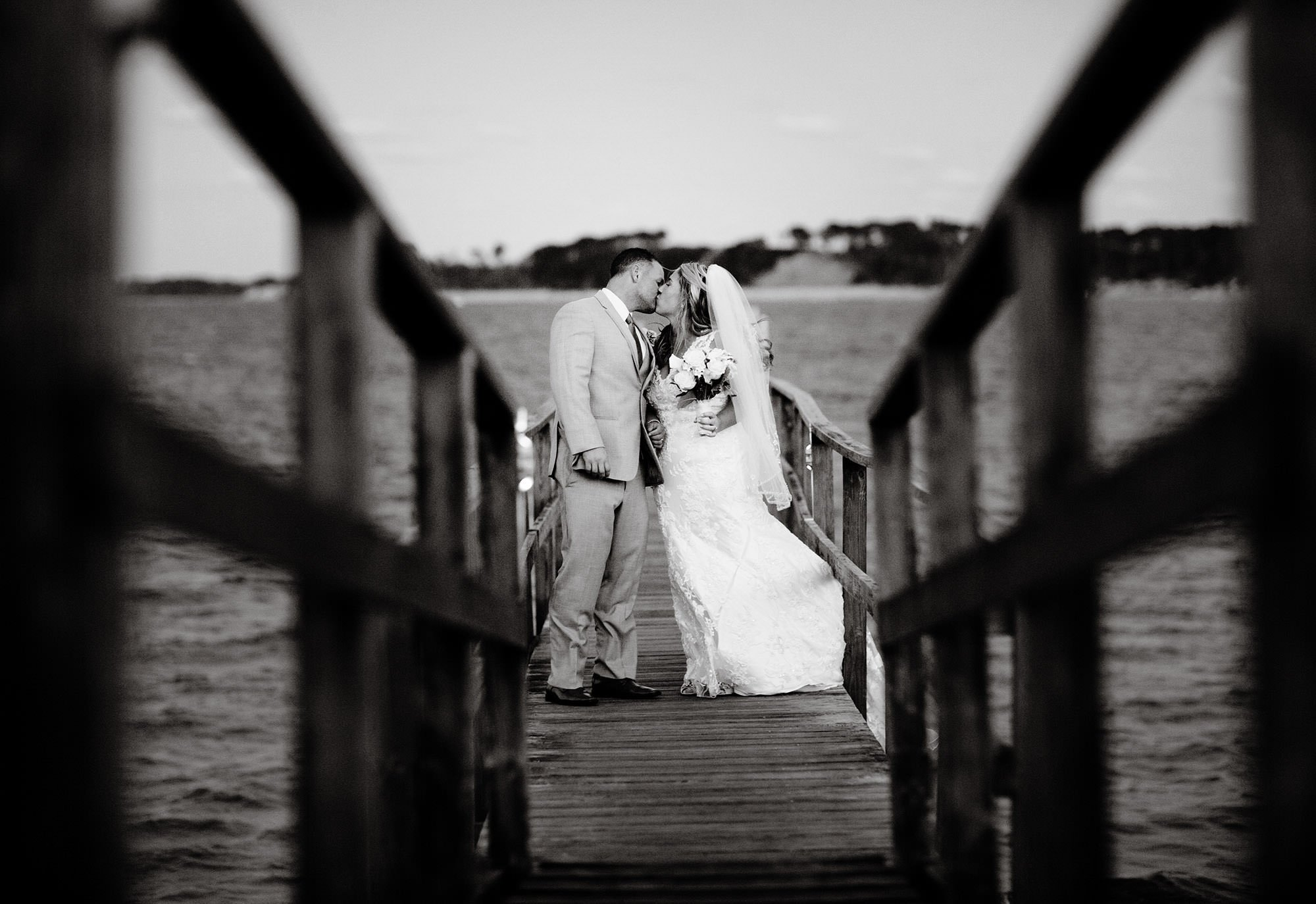The bride and groom kiss on the dock at their Wequassett Resort and Golf Club Wedding in Harwich, MA
